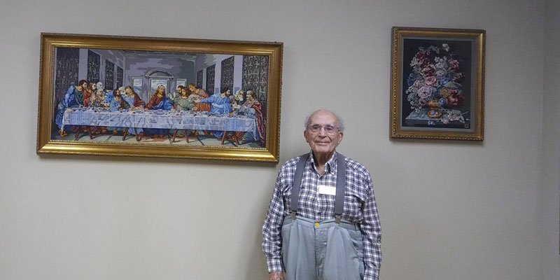 Al, with two of his needlepoint works, on display in the Bank Room.