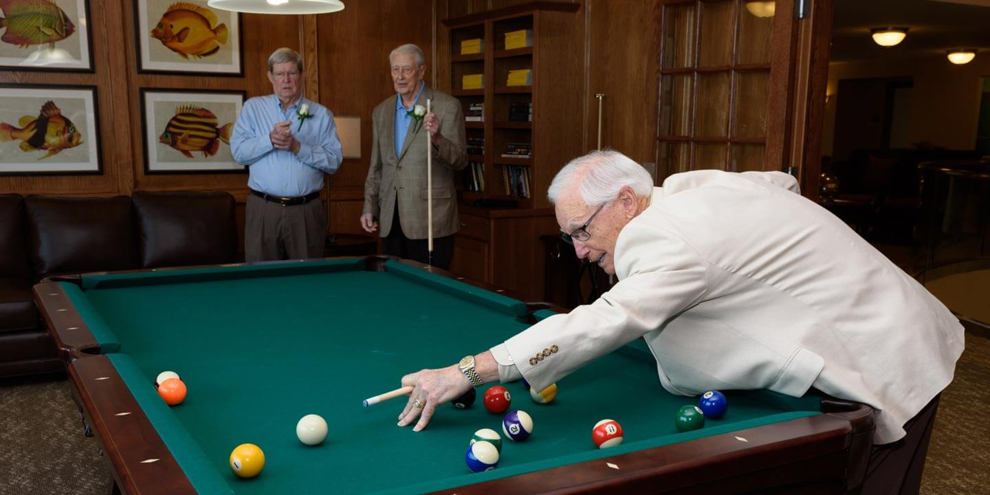 Senior friends playing billiards together.