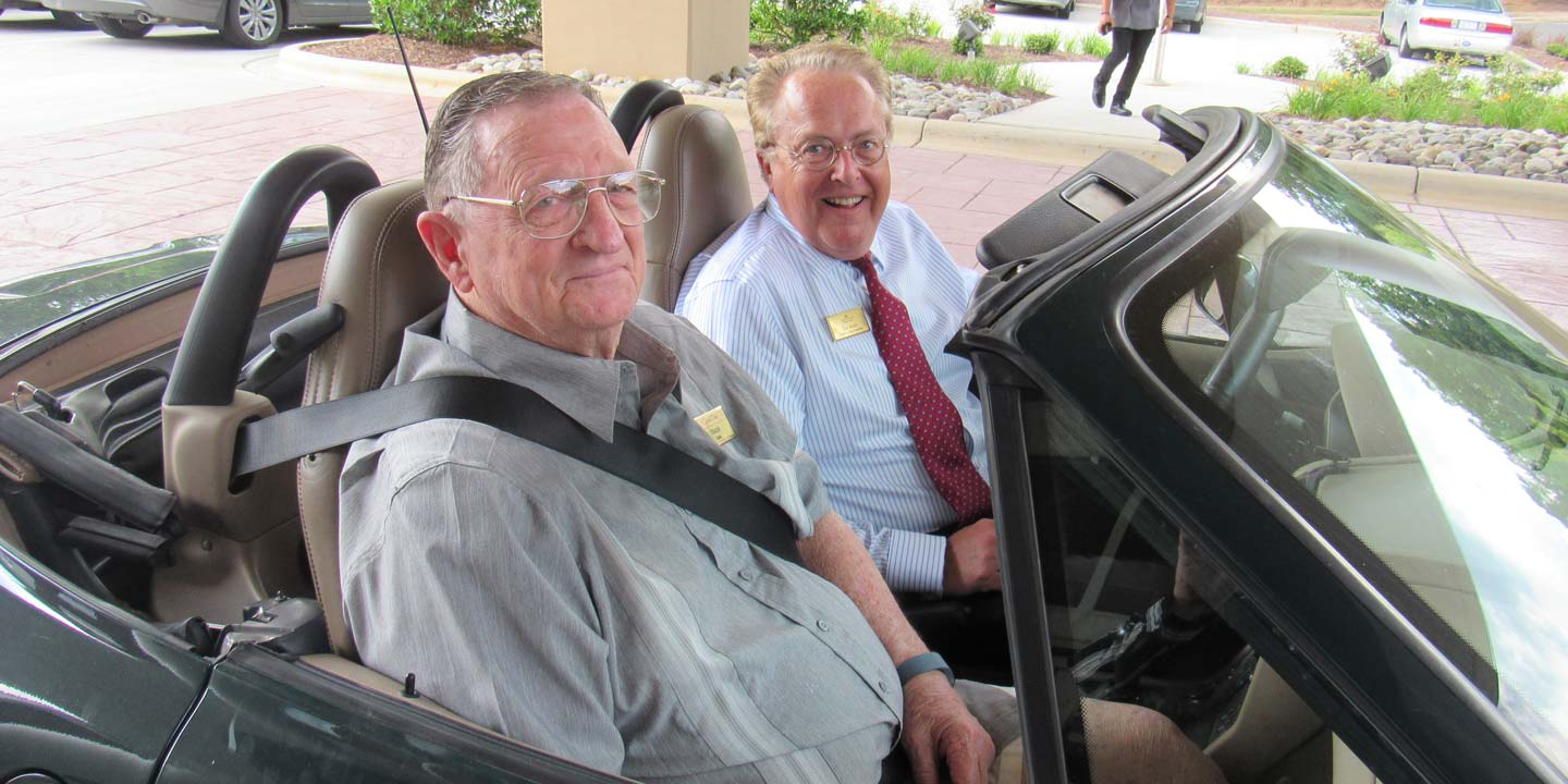 Seniors driving around in their convertible car
