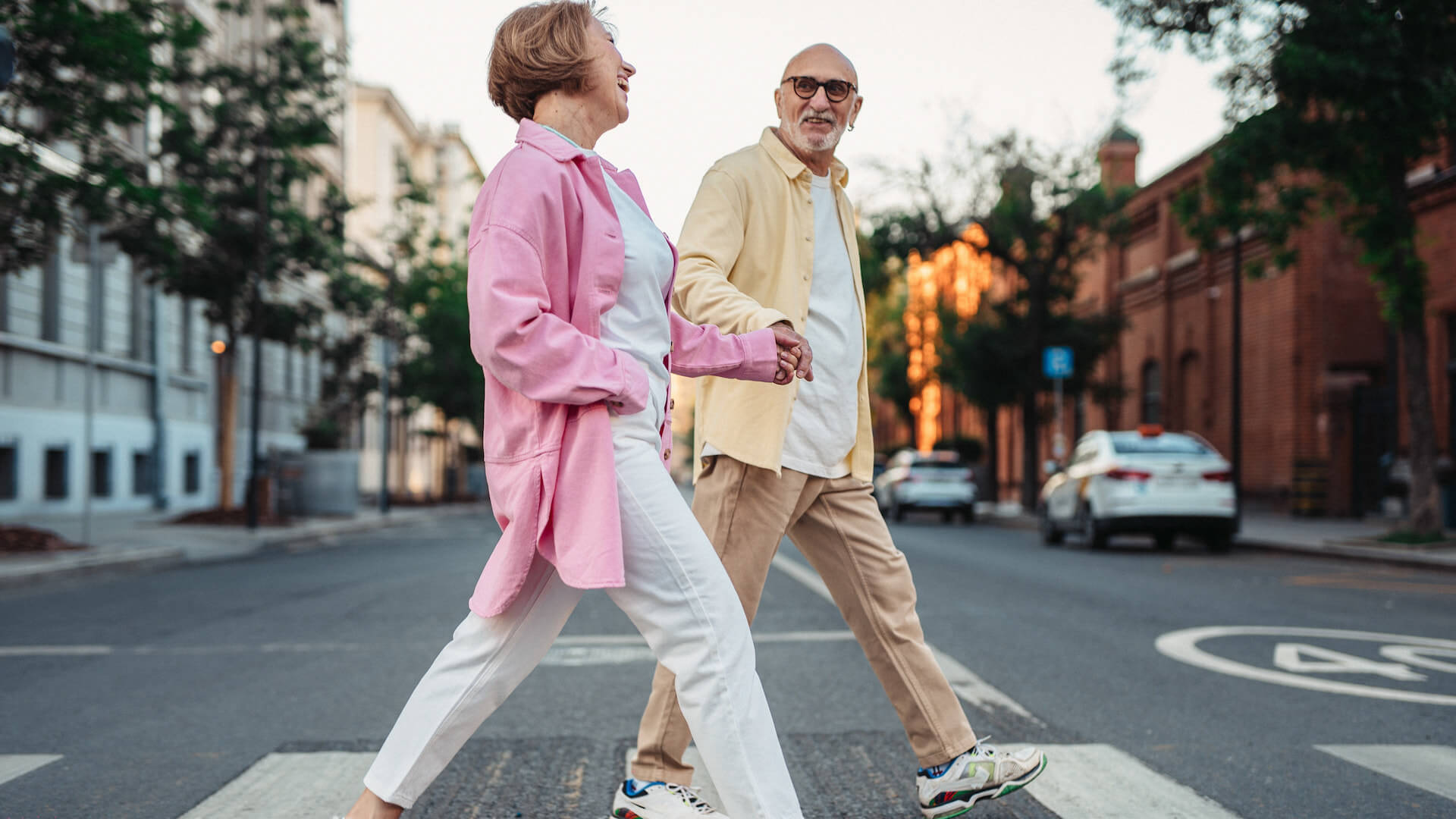 Happy Elderly Couple Holding Hands while Crossing on the Pedestrian Lane