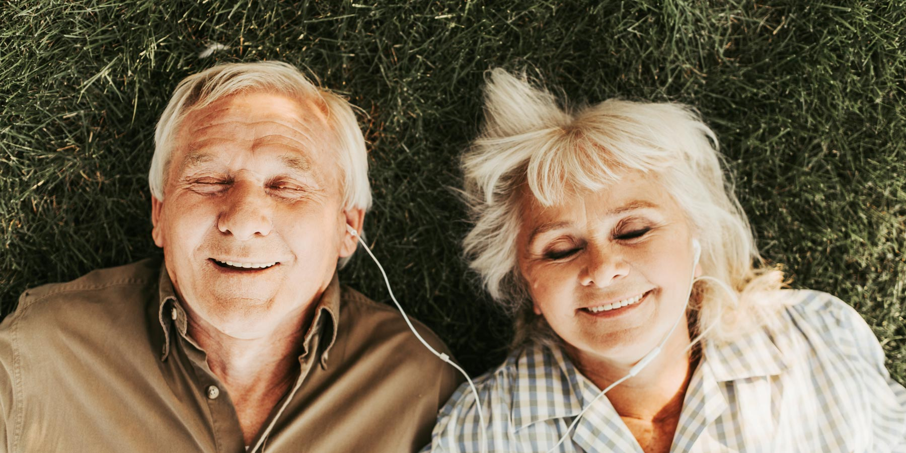 Senior couple laying in the grass listening the music.