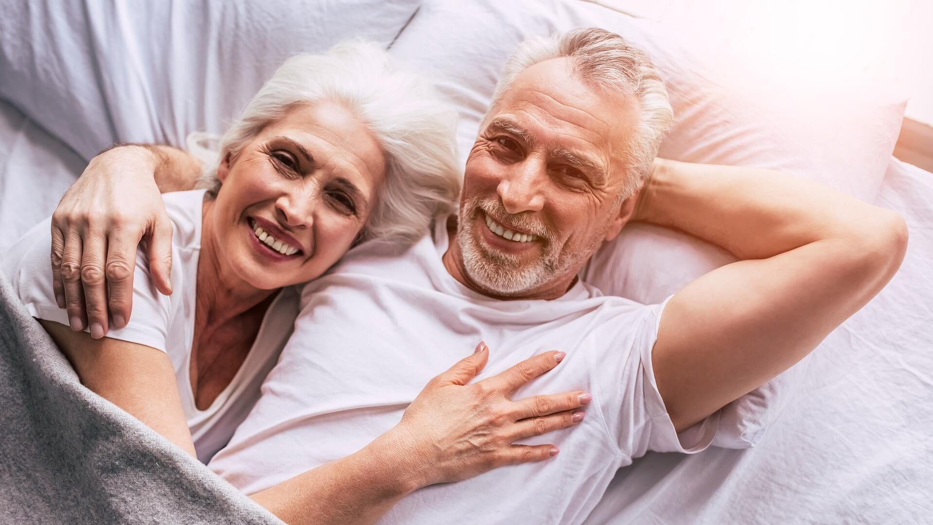 smiling elderly couple laying on the bed