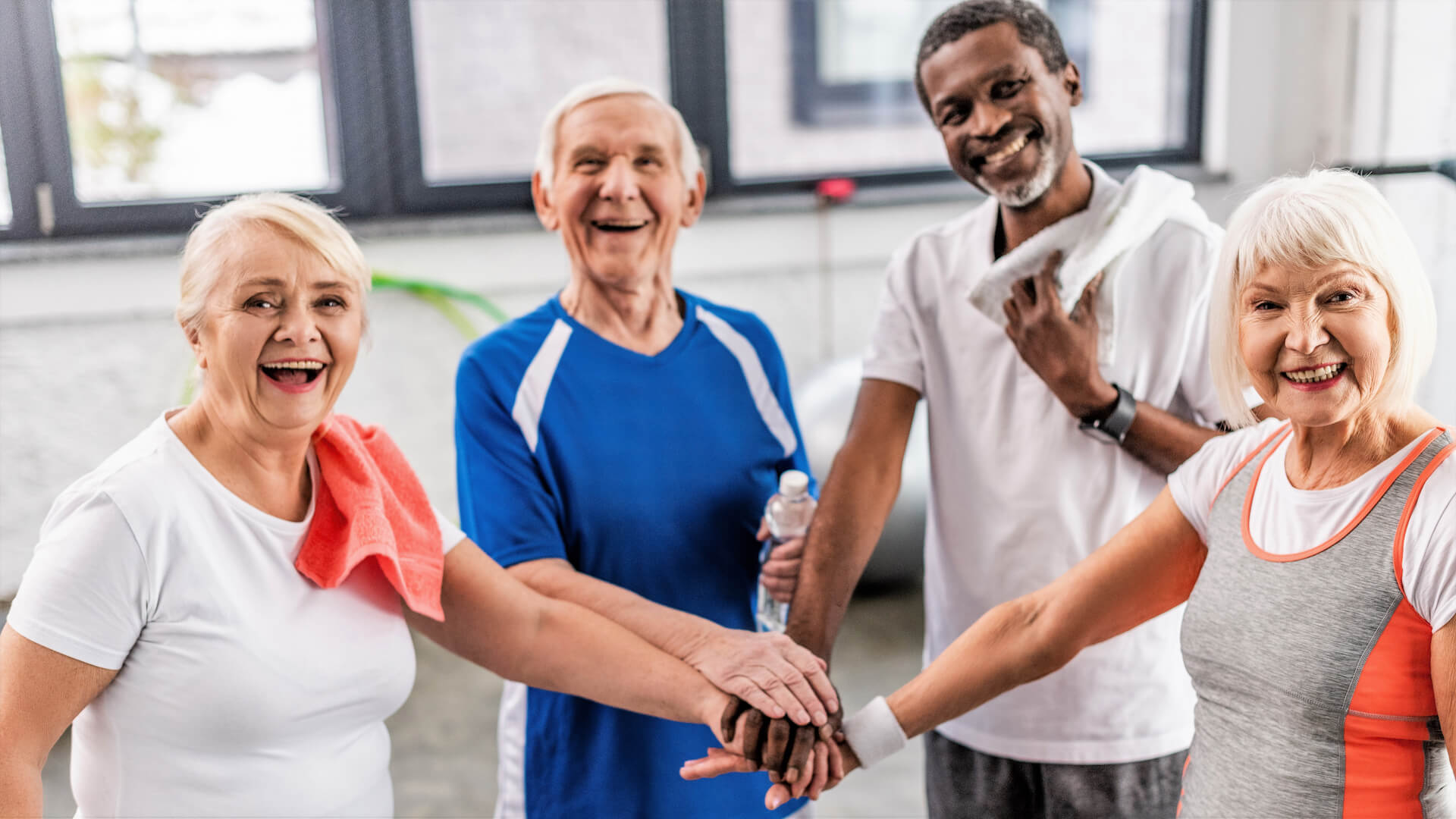 laughing senior multiculutral sportspeople putting hands together at gym