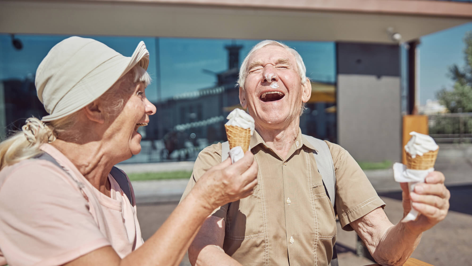 Cheerful married elderly couple with vanilla ice cream waffle cones laughing heartily at the table