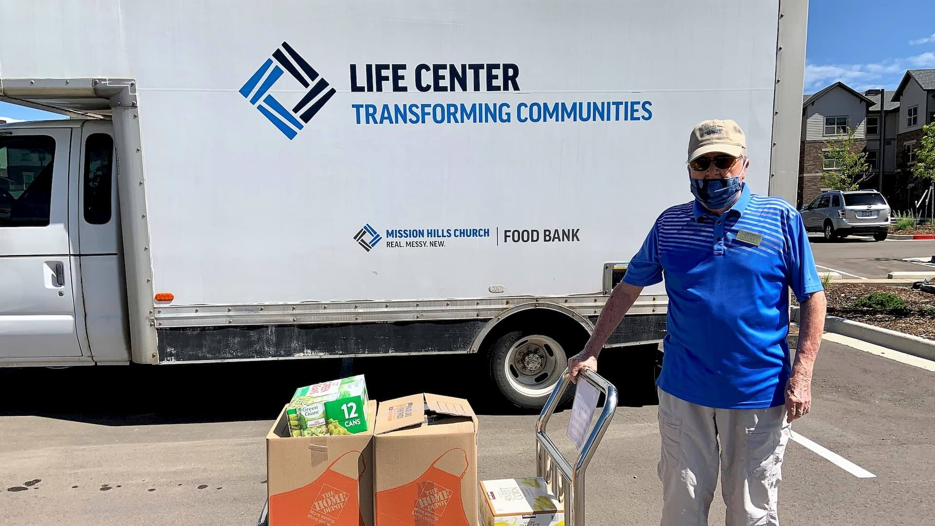 Sky Pointe resident posing with load of food for area food bank