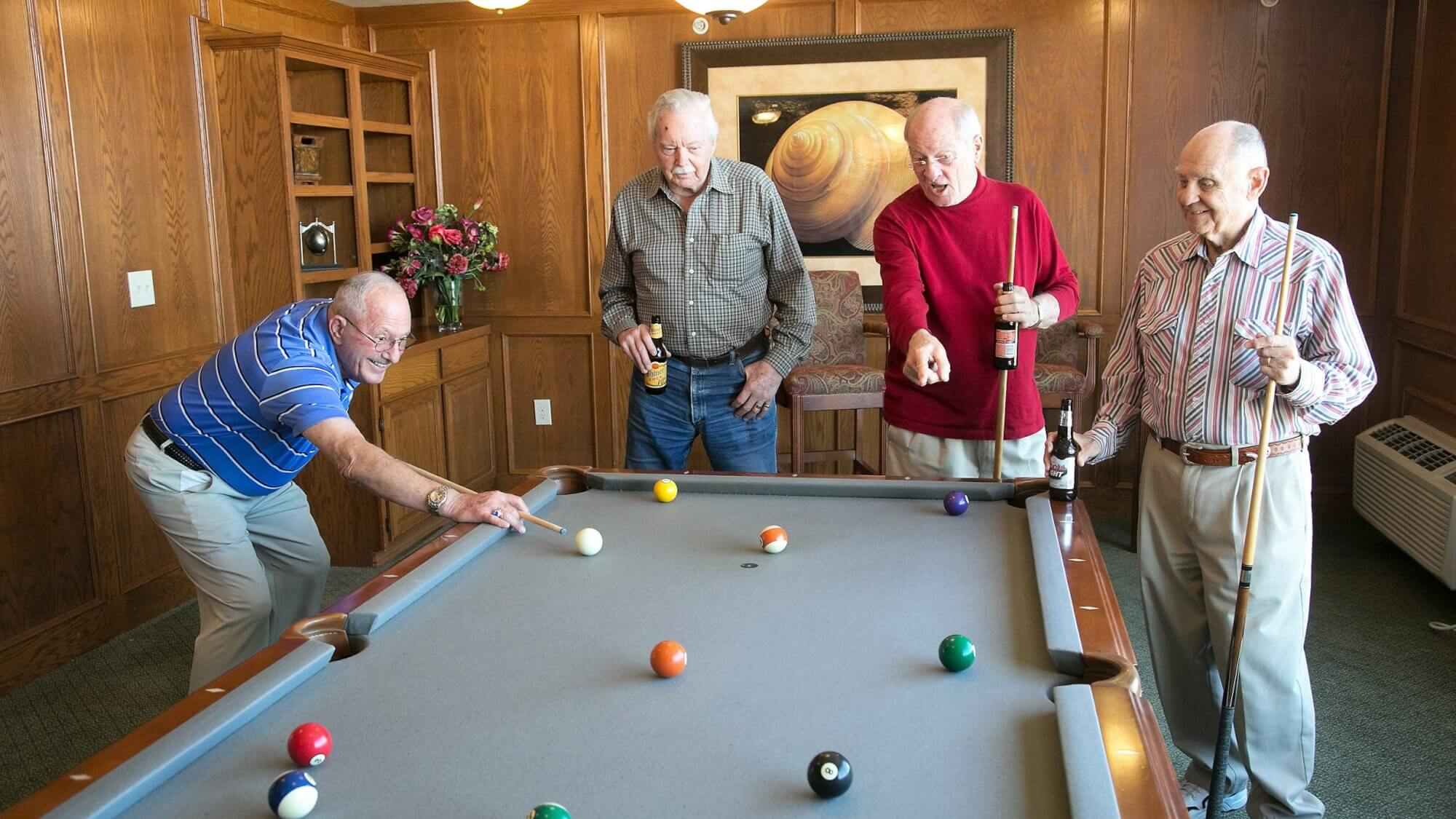 Senior friends playing billiards and drinking beer.