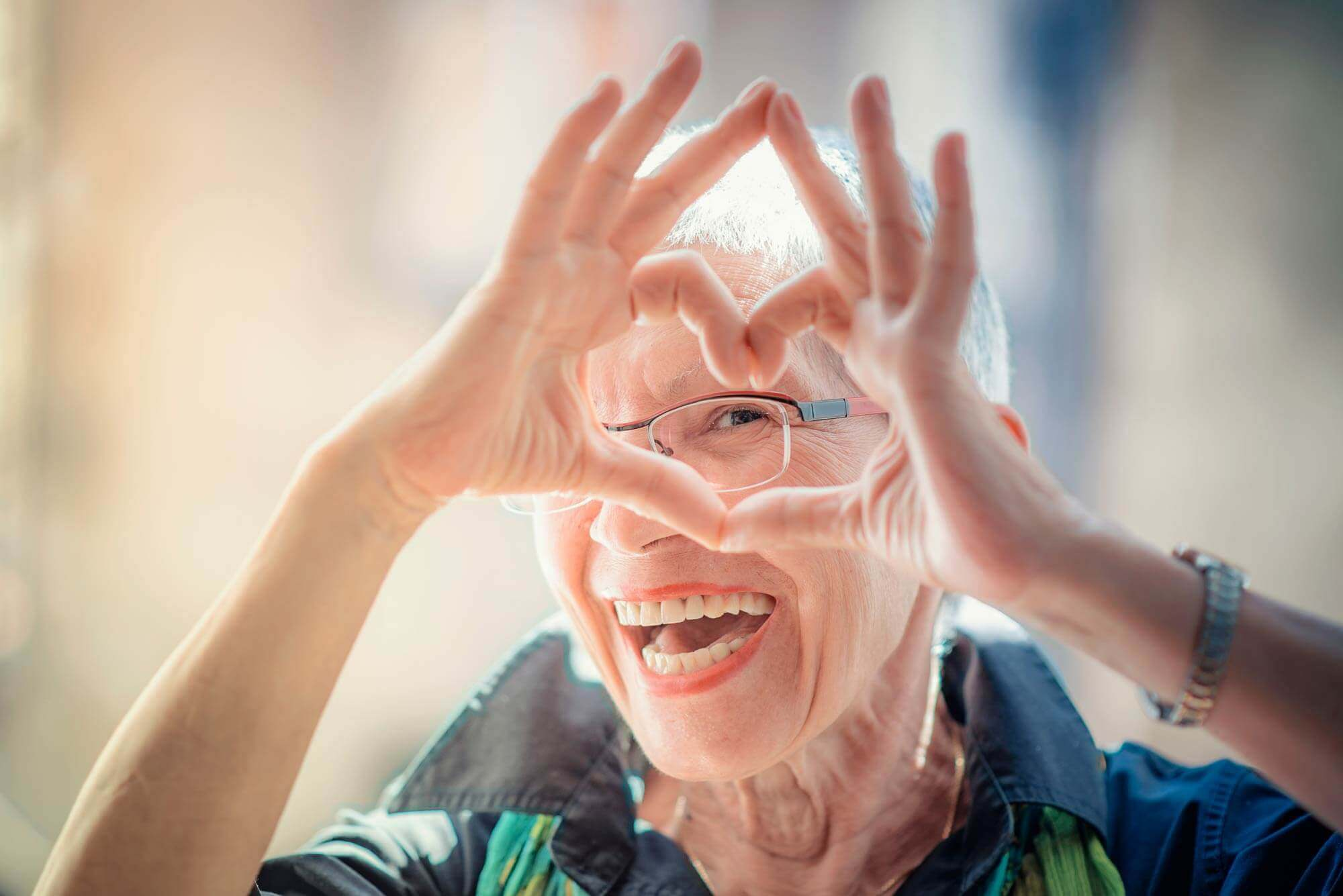 Senior woman with beautiful smile looking through hands shaped like heart