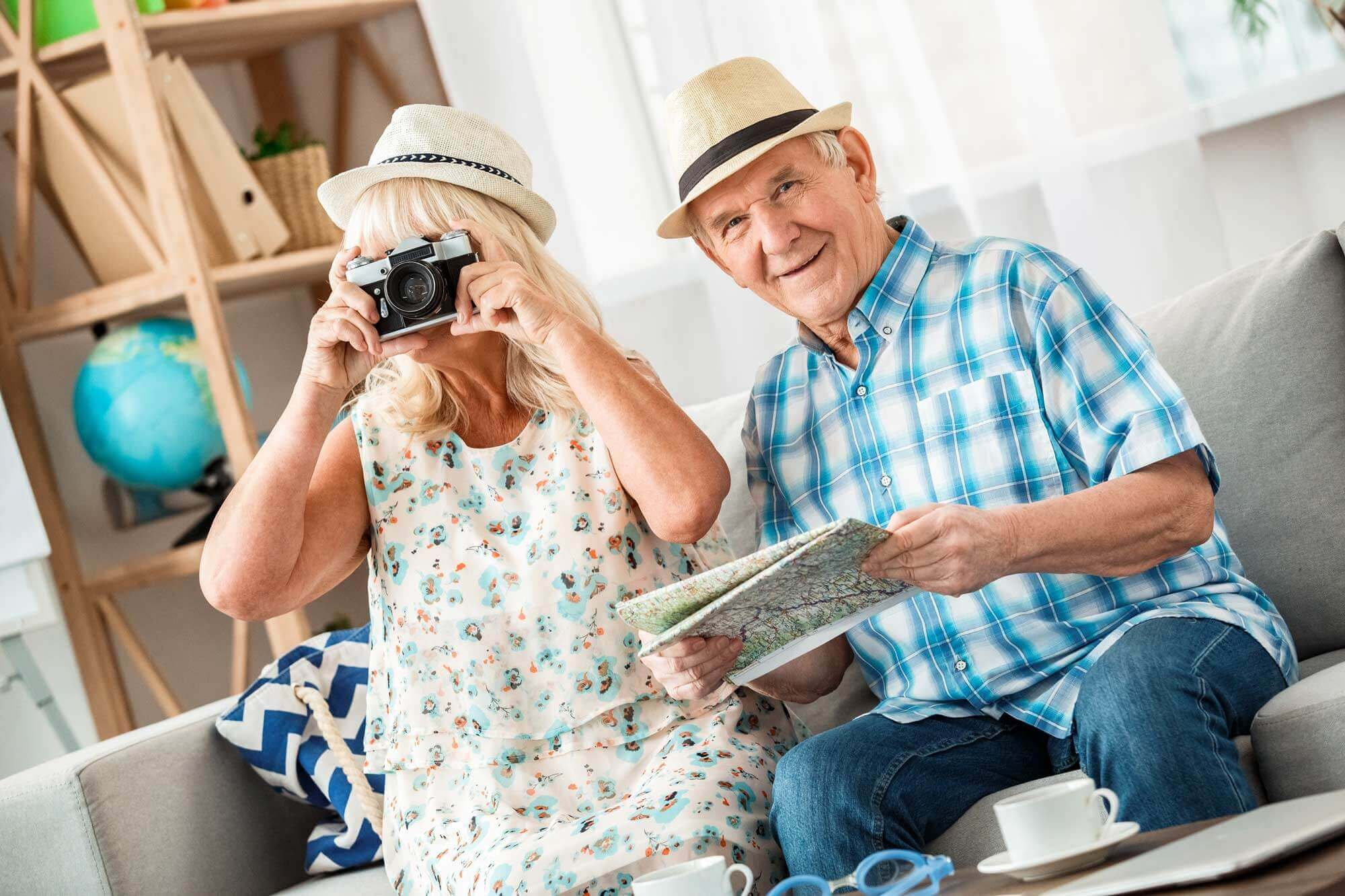 Woman takes photo with camera while husband smiles looking at a map