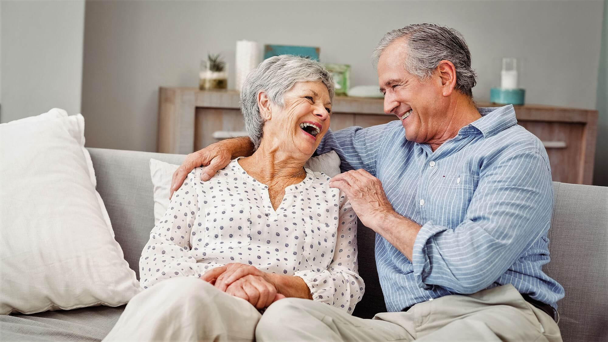 Husband and wife have a laugh together on their couch.