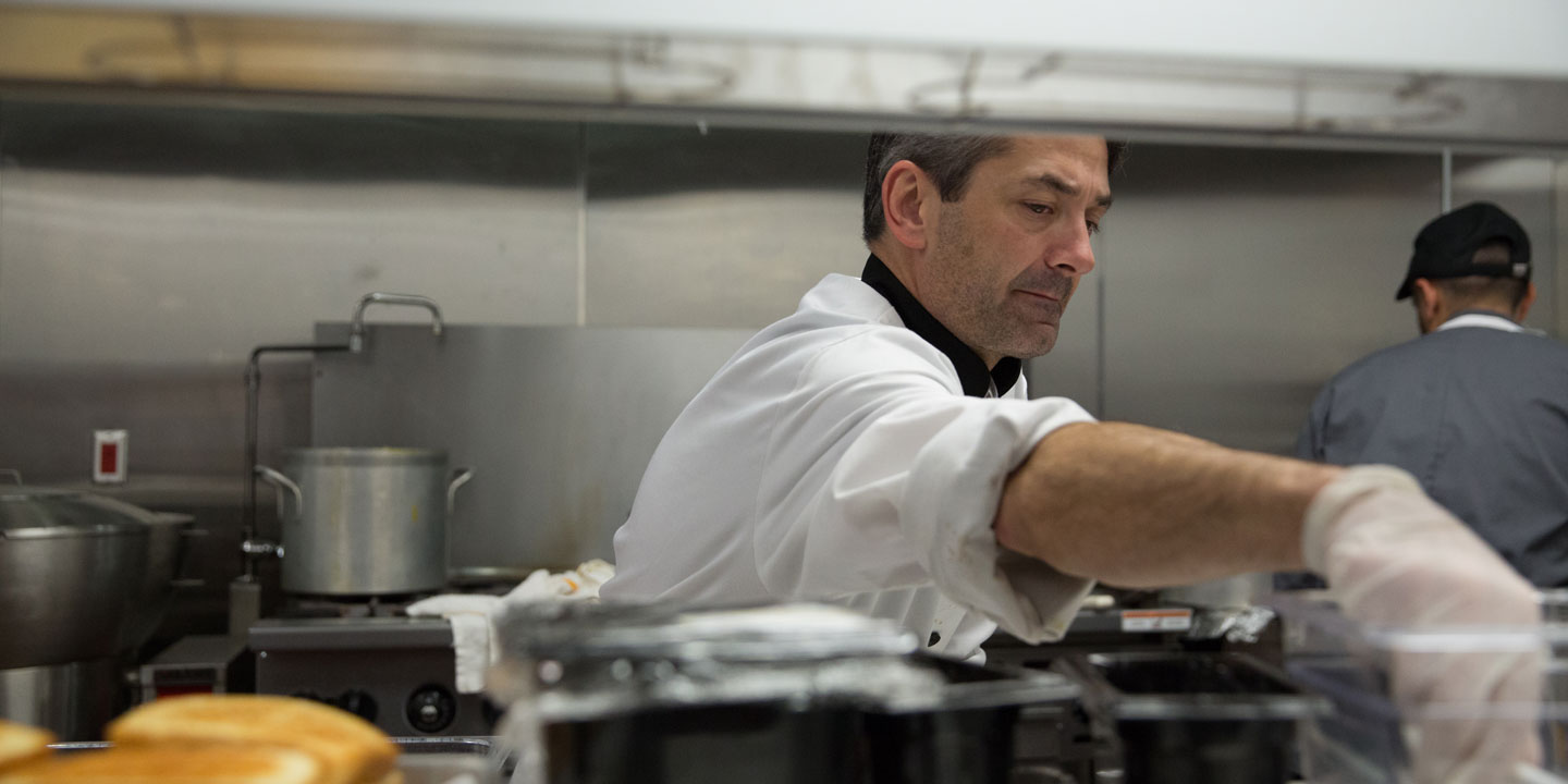 A head chef reaching into a container to get an ingredient to spice up the main dish.