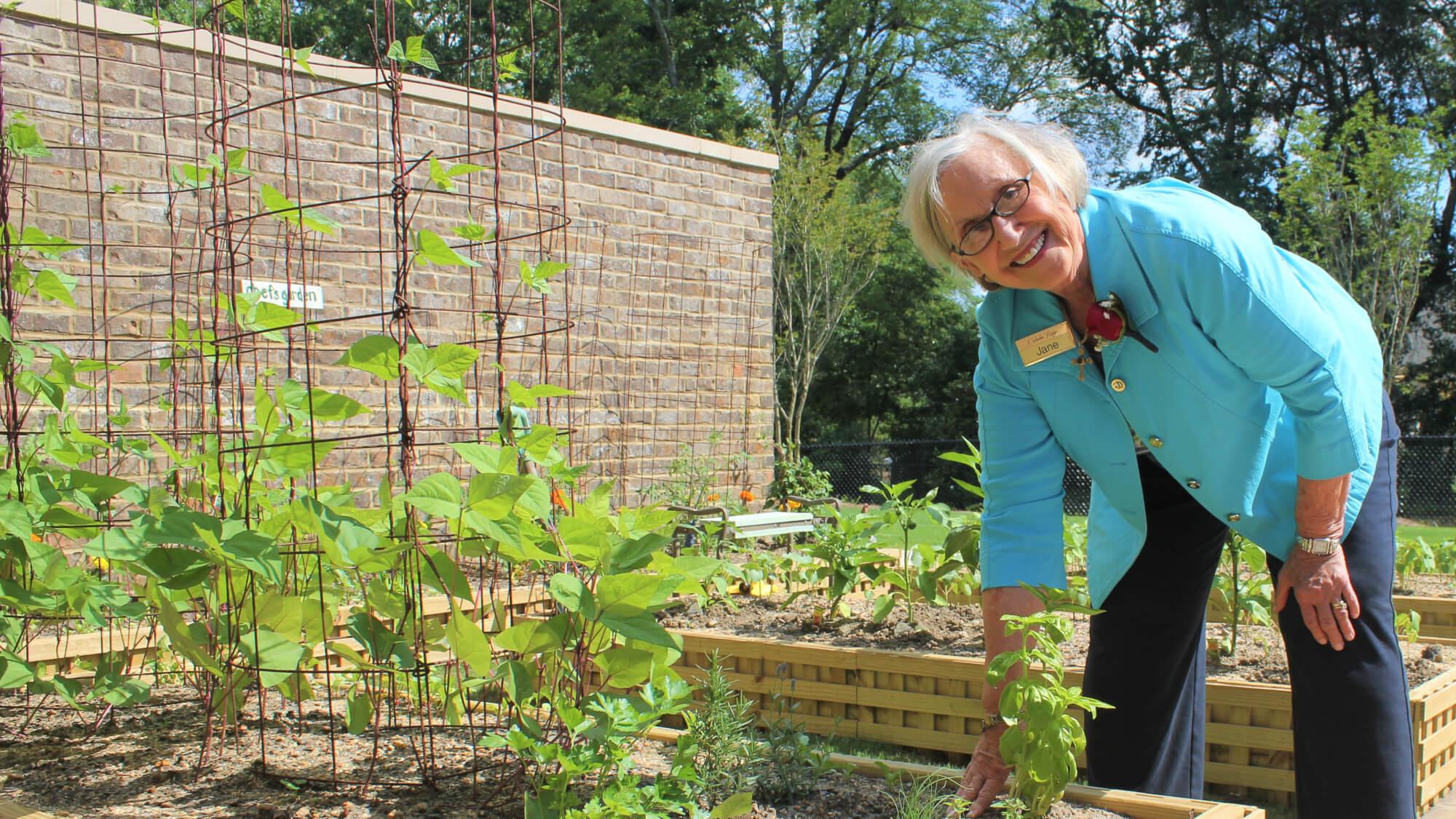 Resident Jane helping tend Chef's Garden