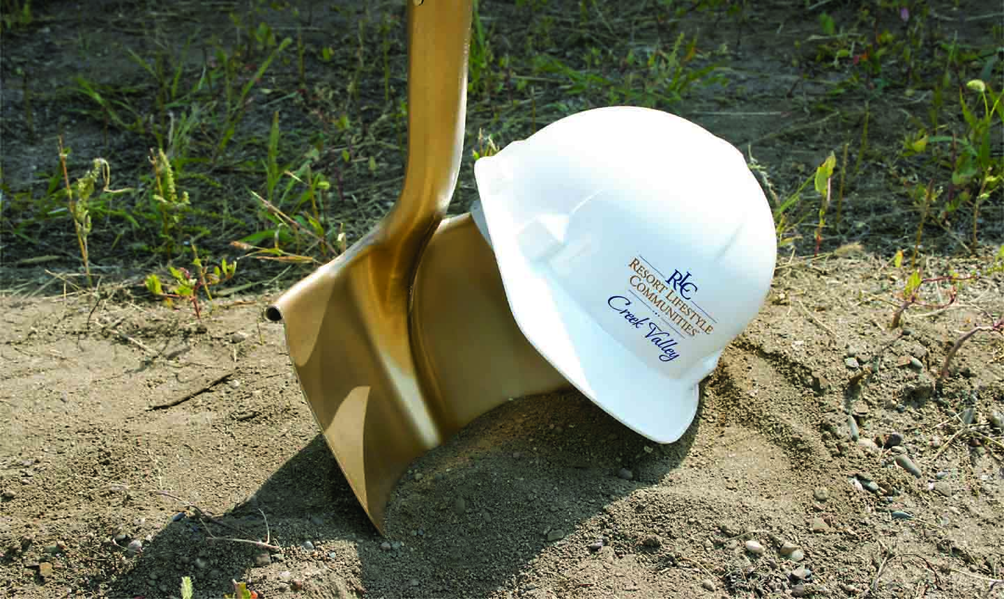 Golden shovel and Resort Lifestyle Communities hard hat to represent the construction being done at Creek Valley