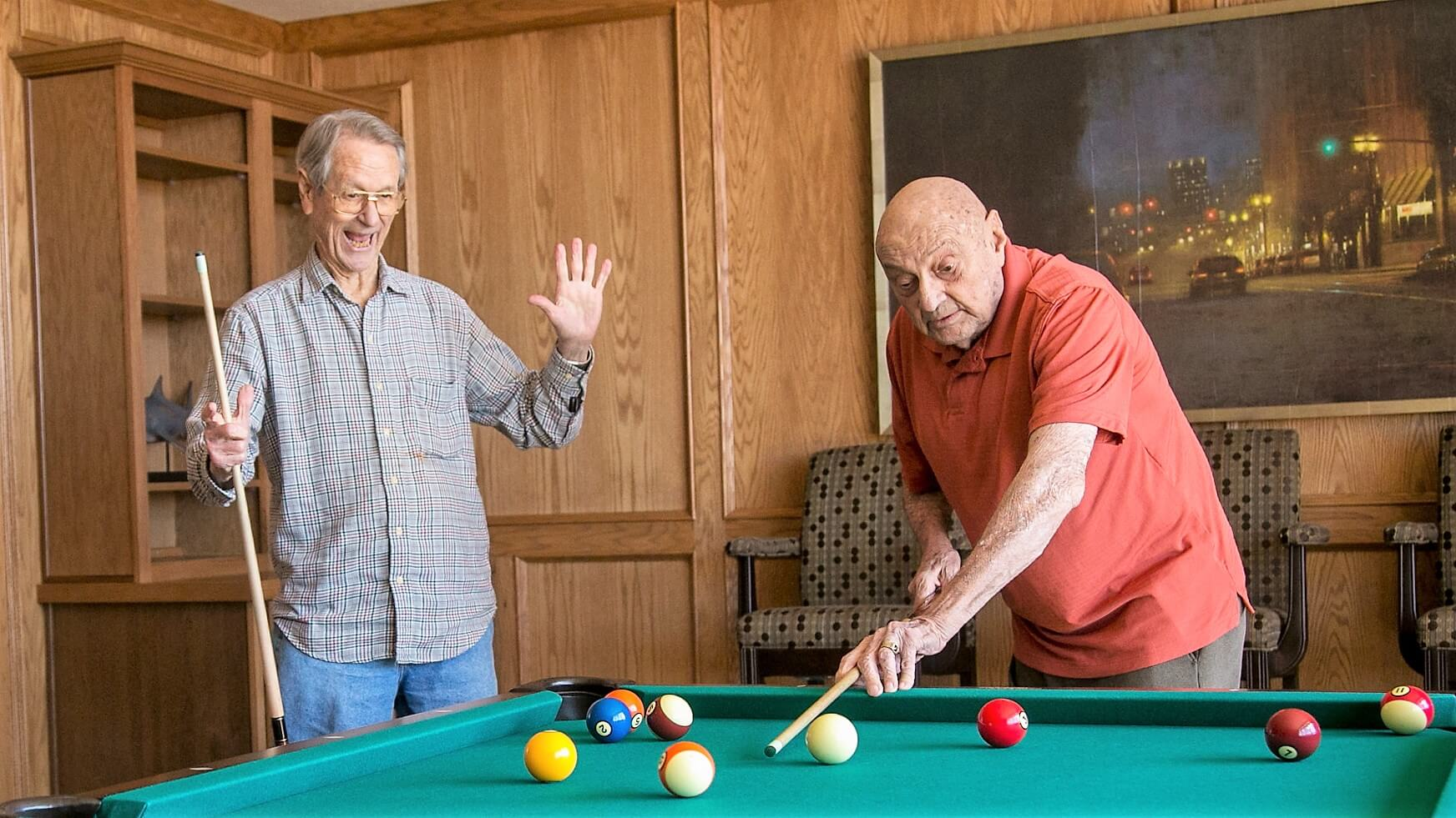 Gentlemen playing a friendly game of pool.