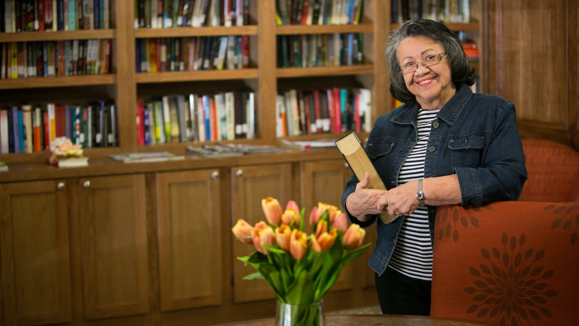 Senior holding a book in Emerald Oaks Library.