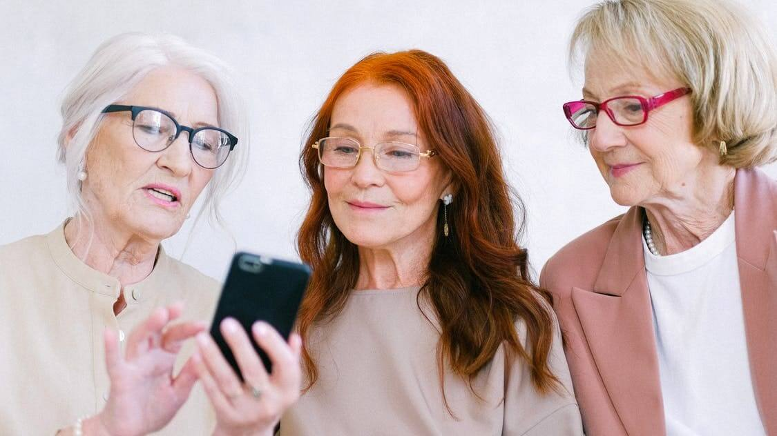 Three professionally dressed seniors viewing a mobile phone