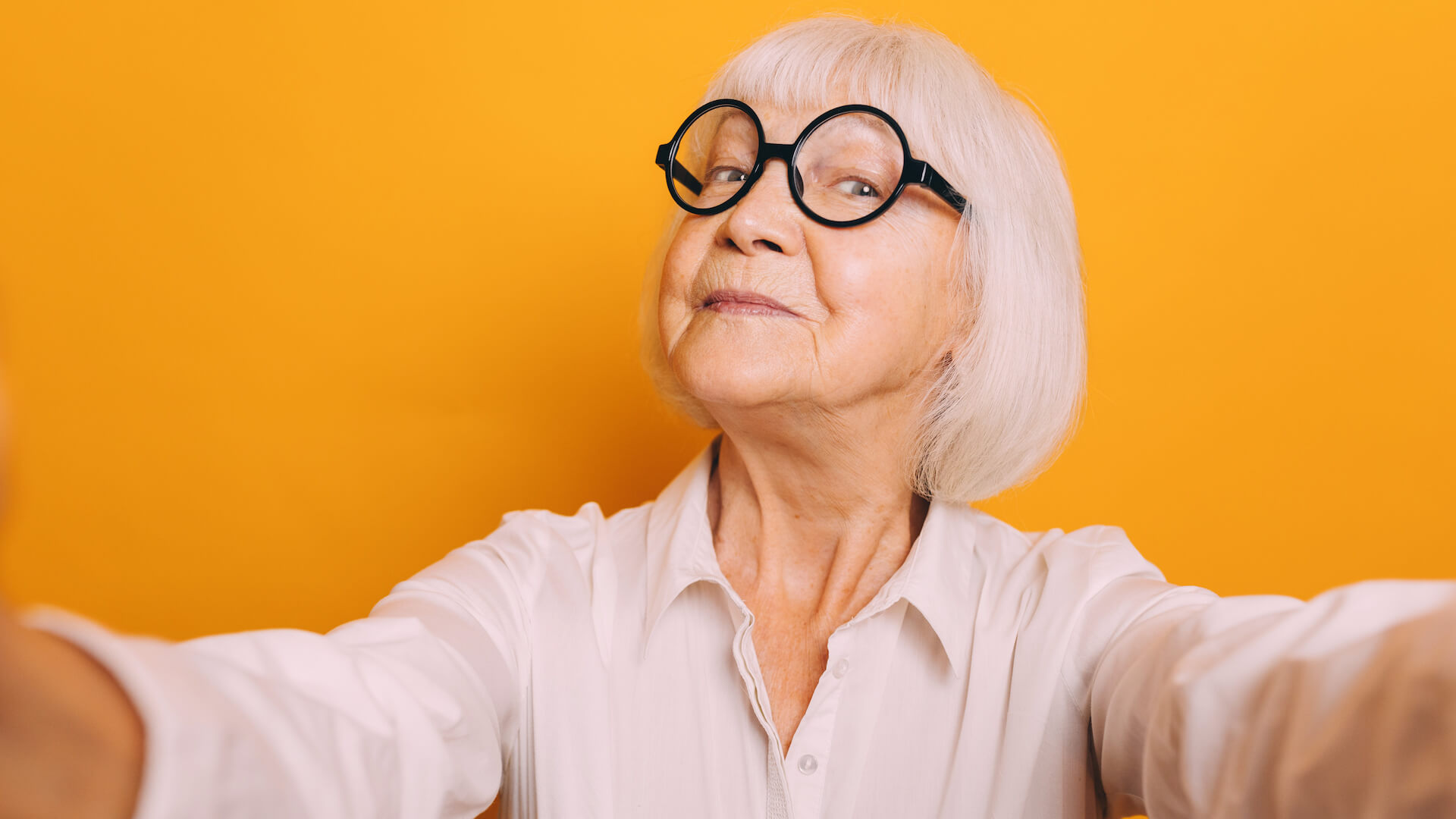 Portrait of elderly woman with short white hair wearing white glasses and light blouse holding camera and taking selfie. Old Woman isolated over orange background