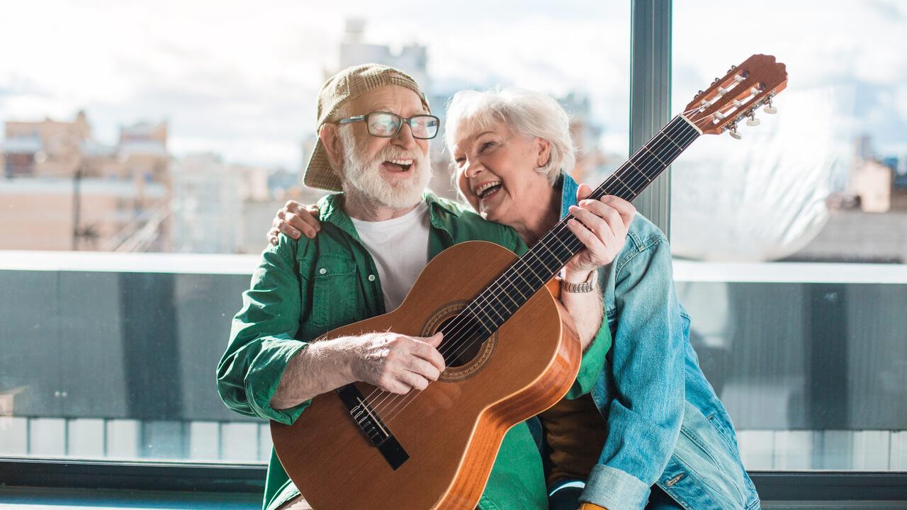 senior couple laughing while playing guitar