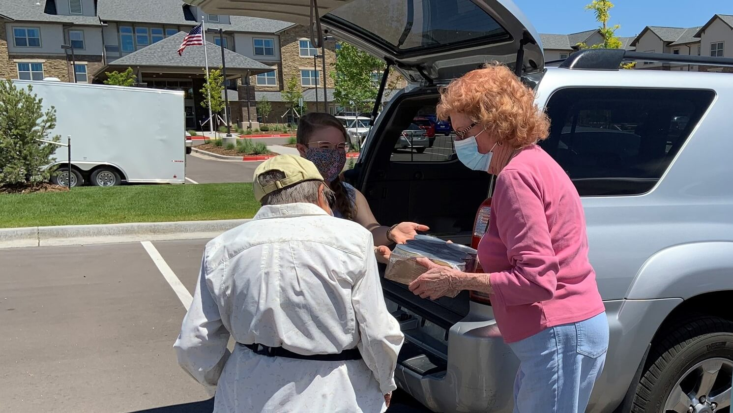 Seniors receiving groceries from a delivery girl.