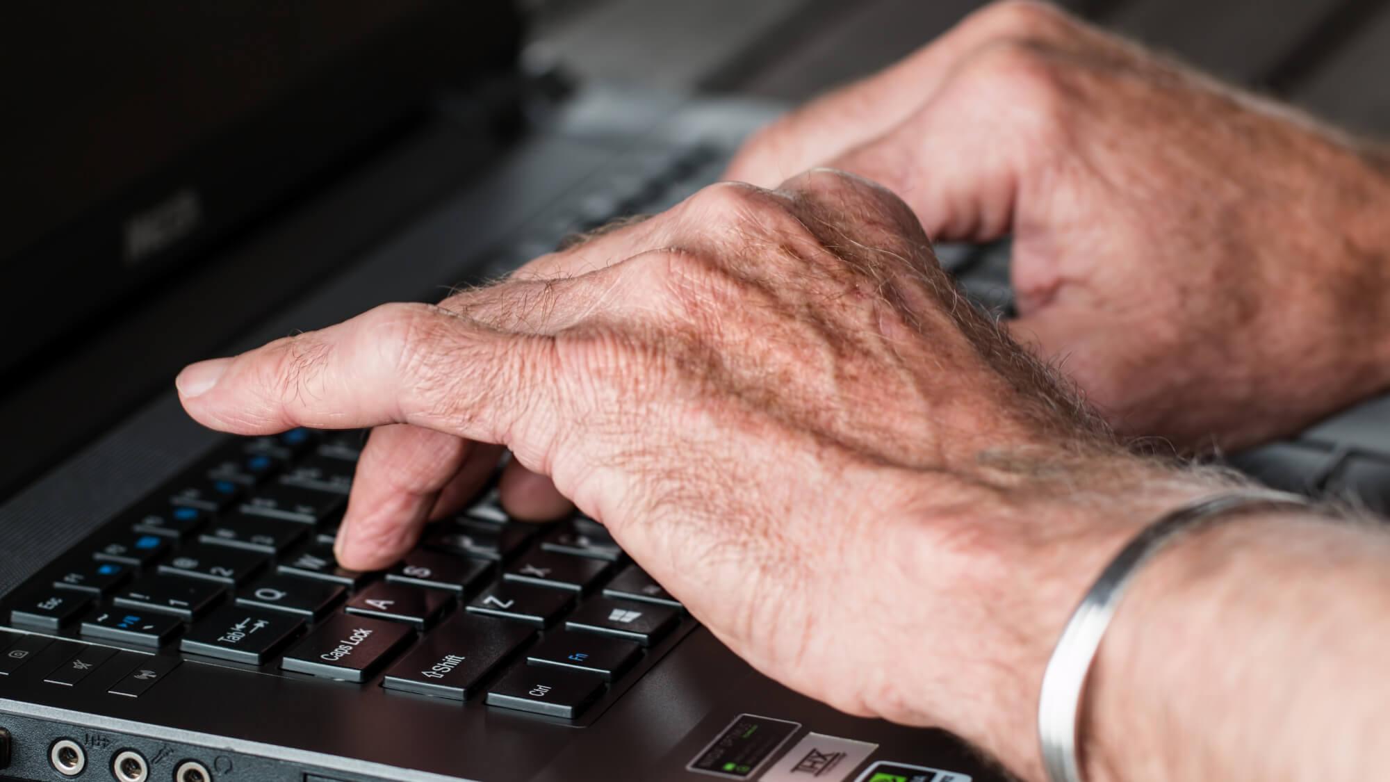 elderly hands typing on laptop