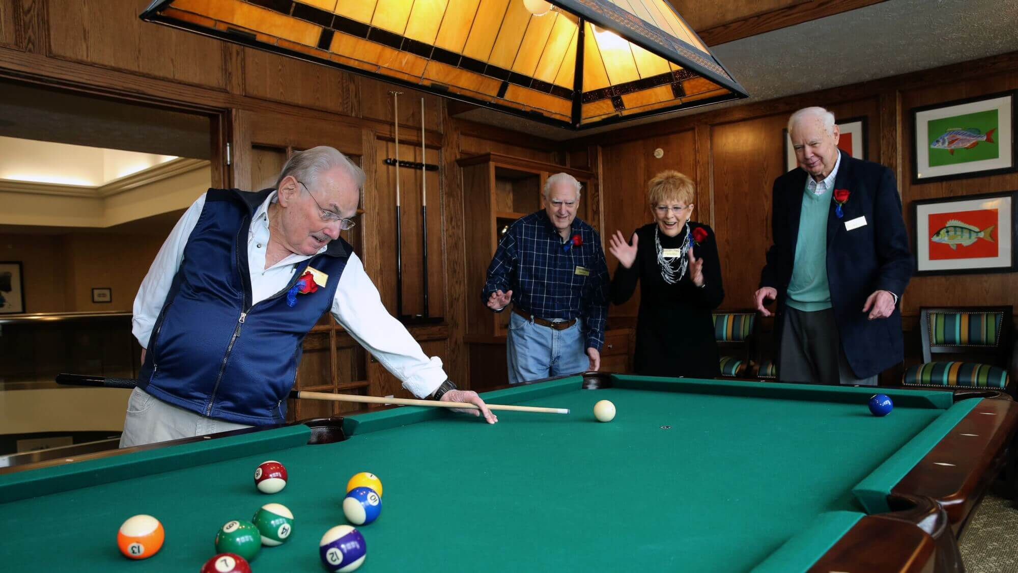 Residents cheering on a trick billiards shot in the pool hall at Lake Forest Village.