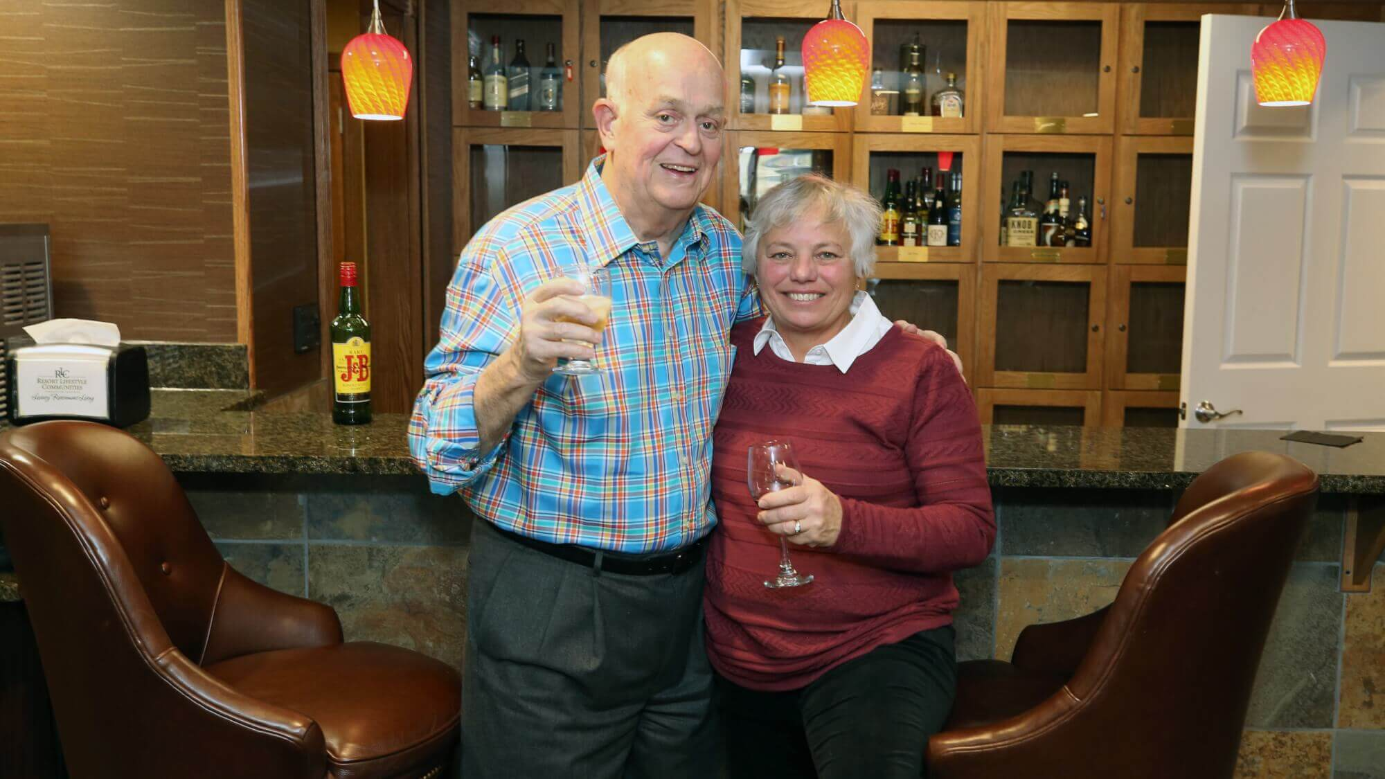 Resident couple enjoying a glass of scotch and wine in the happy hour lounge.