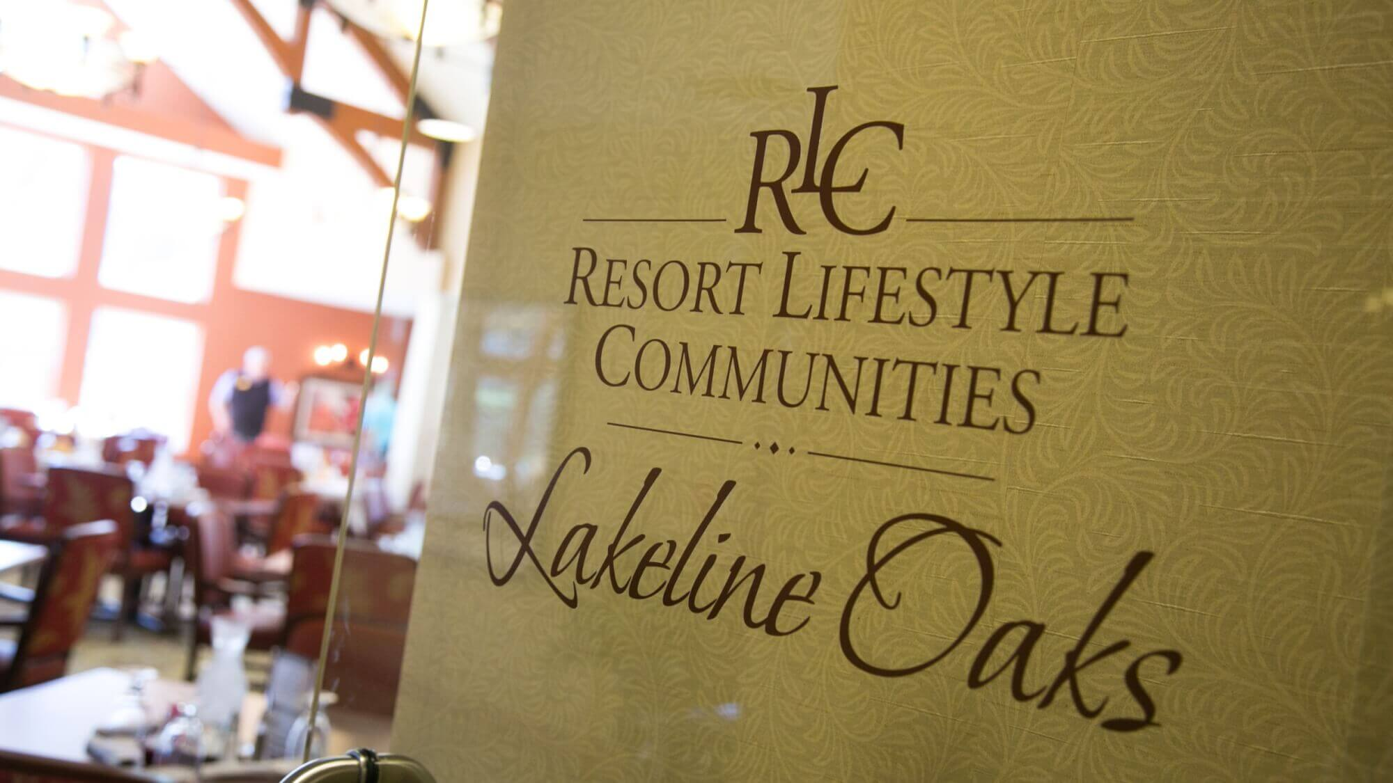 Glass door etched with Lakeline Oaks logo entering the grand dining hall