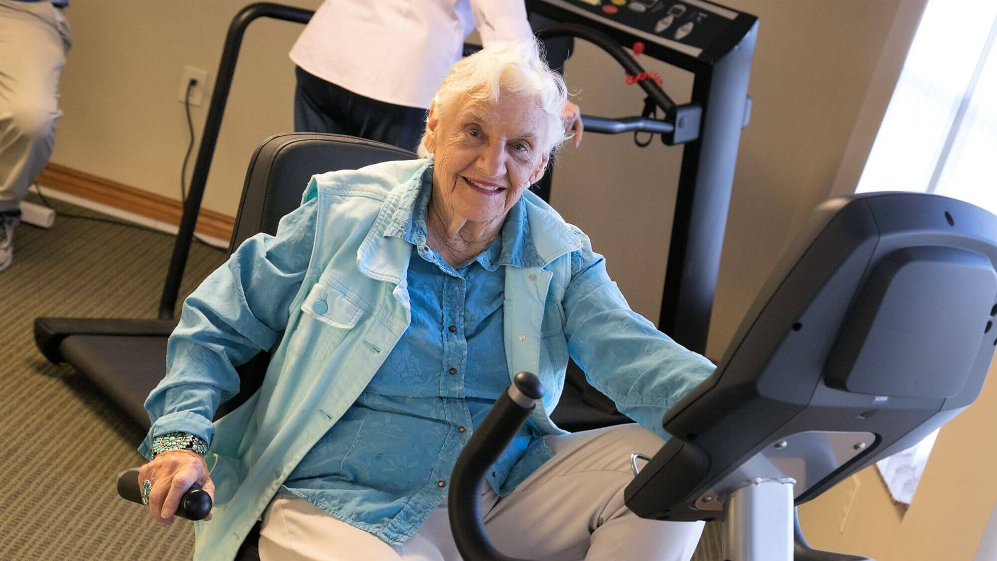 Senior riding a machine bike at the fitness center.