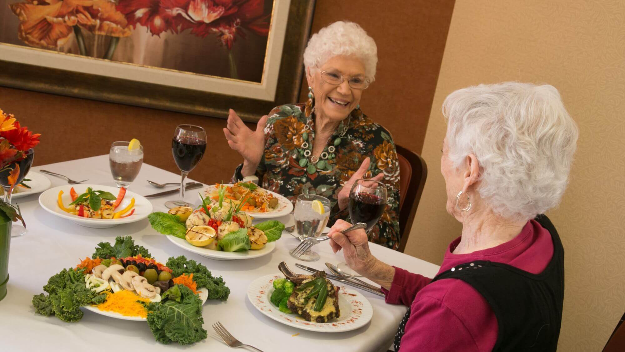 Two ladies dine together and share laughs over a glass of wine during fine dining at Lakeline Oaks in Cedar Park Texas.
