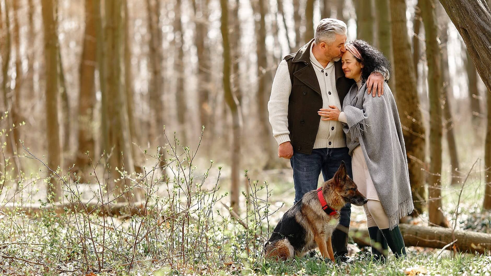 Senior couple spending time in the forest with their dog.