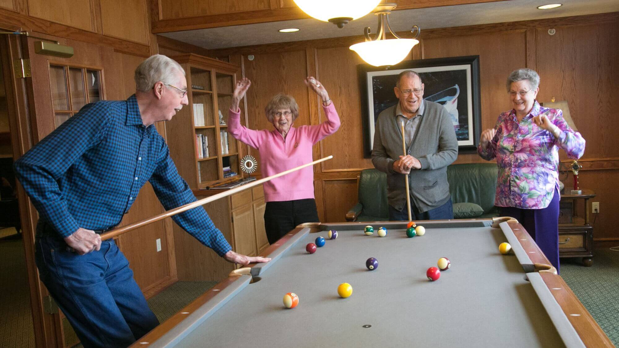 Residents enjoy a game of pool in the billiards room at Maple Ridge.
