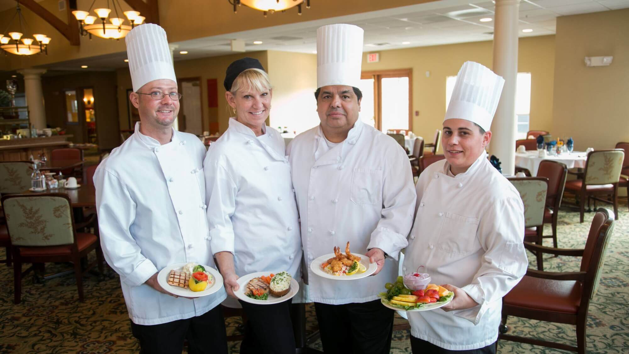 Culinary team at Maple Ridge poses with four delectable fine dining dishes