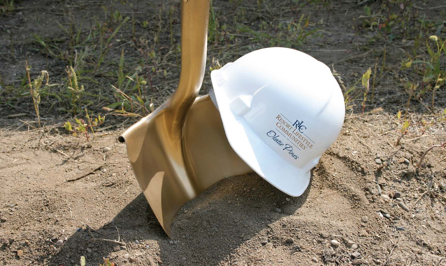 Golden shovel and Resort Lifestyle Communities hard hat representing Okatie Pines construction.