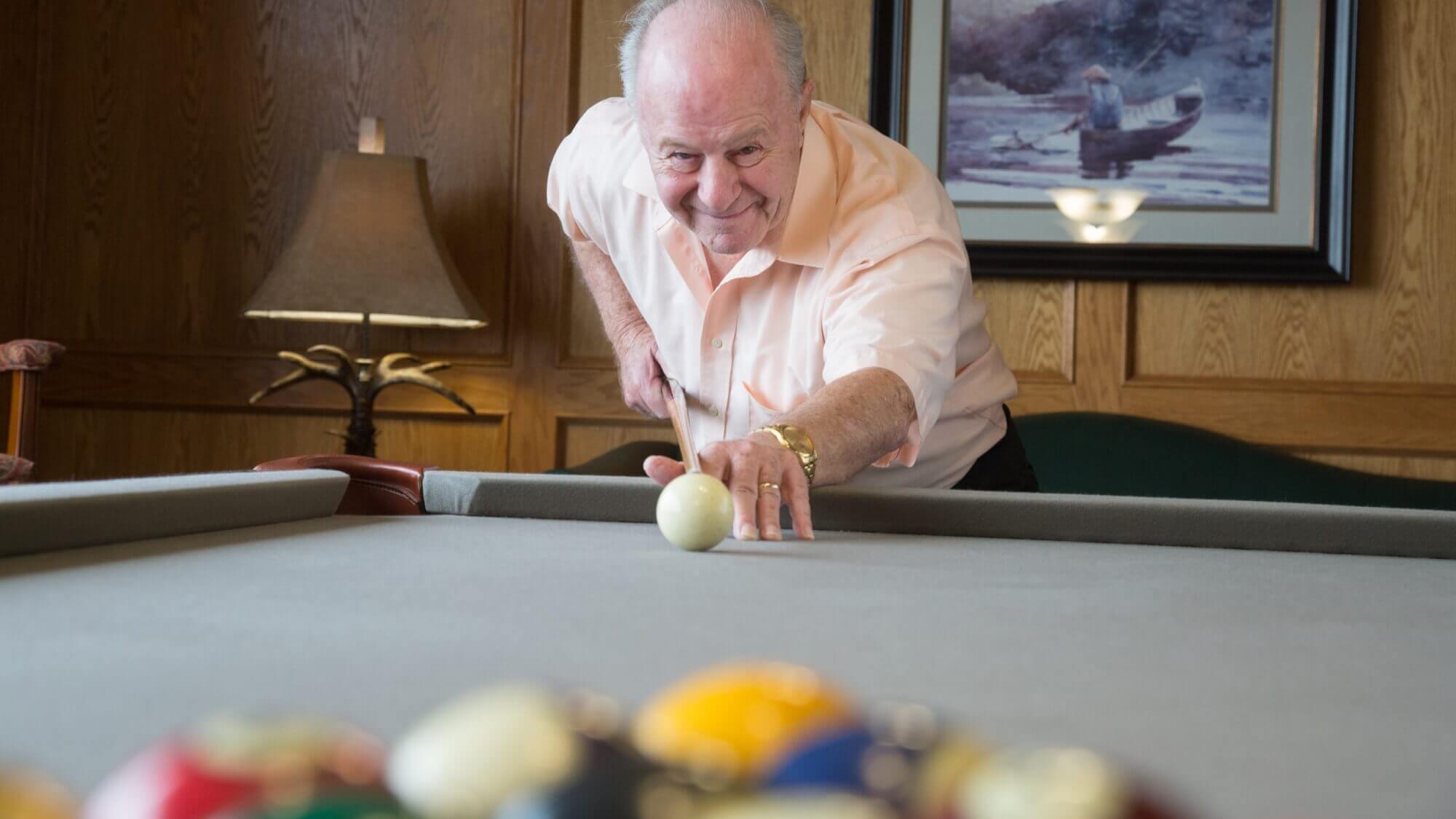 Senior playing billiards at Provident Crossings.