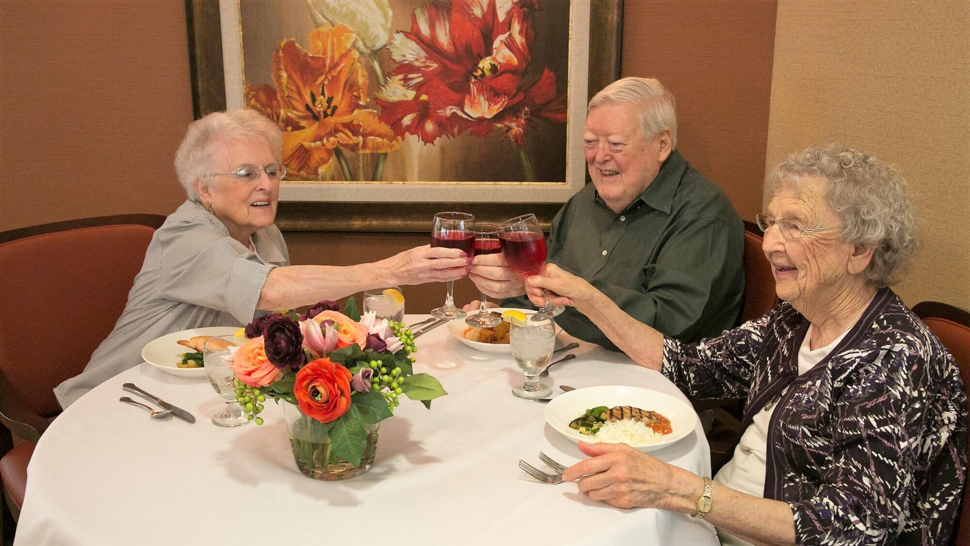 Senior friends dining together, cheering their glasses.
