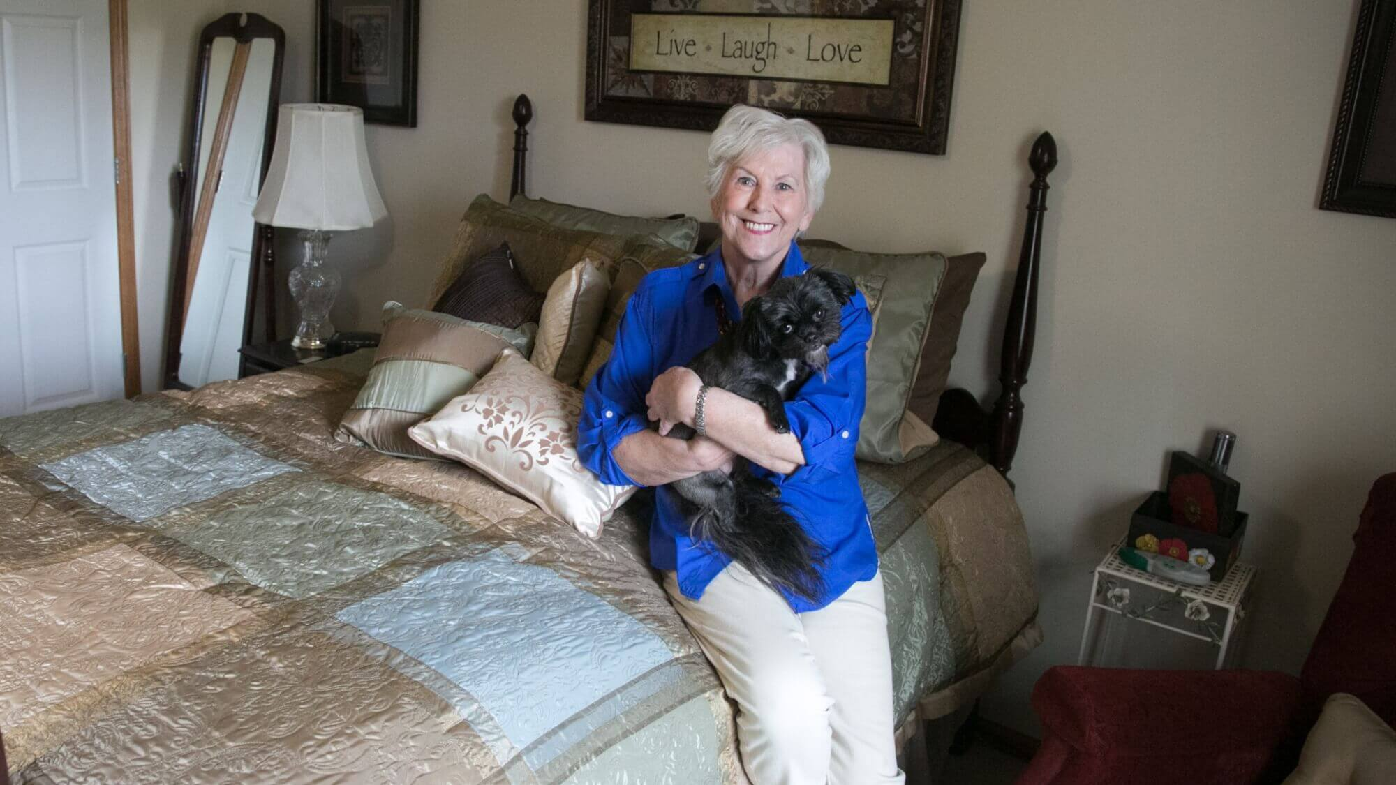 Woman resident smiling while she sits on her bed holding her dog sitting on her bed holdin