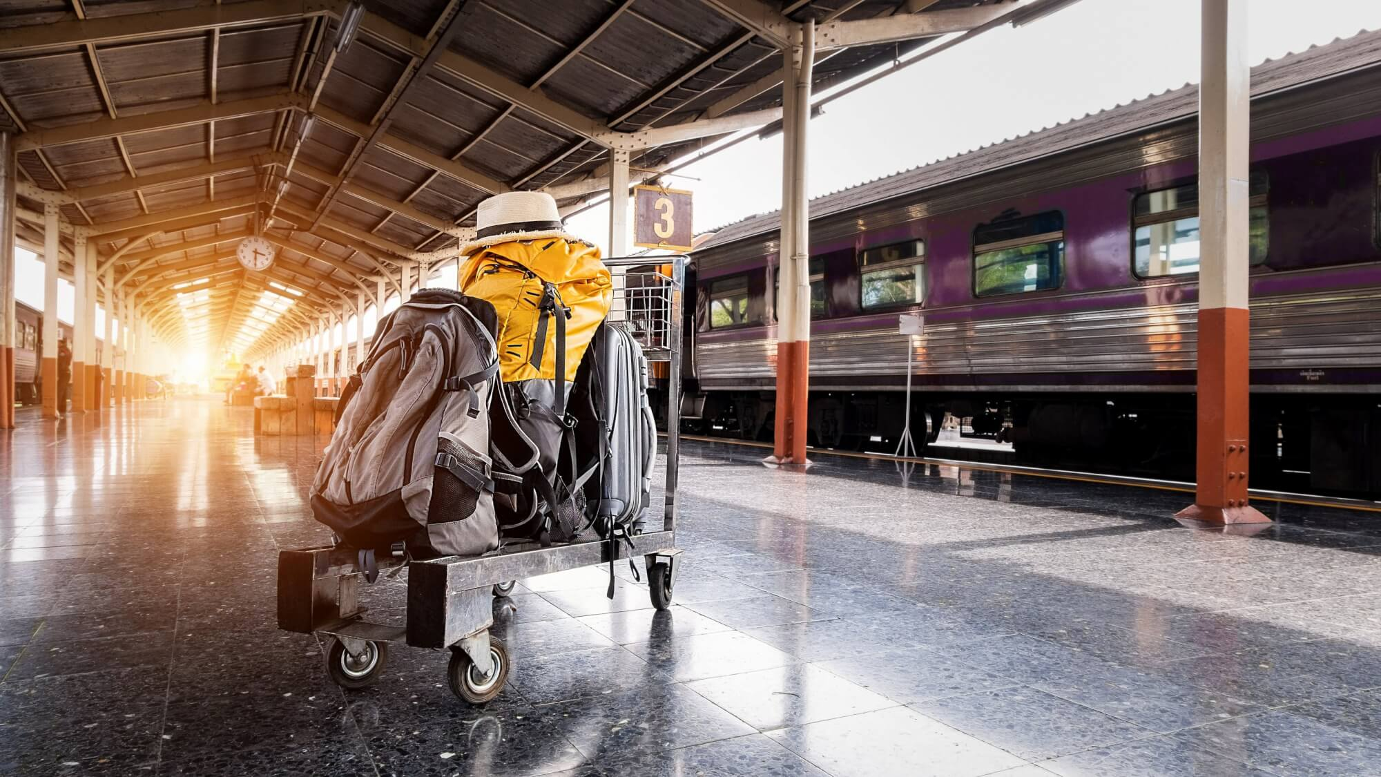 Several Bags on Trolley Near Train in Station