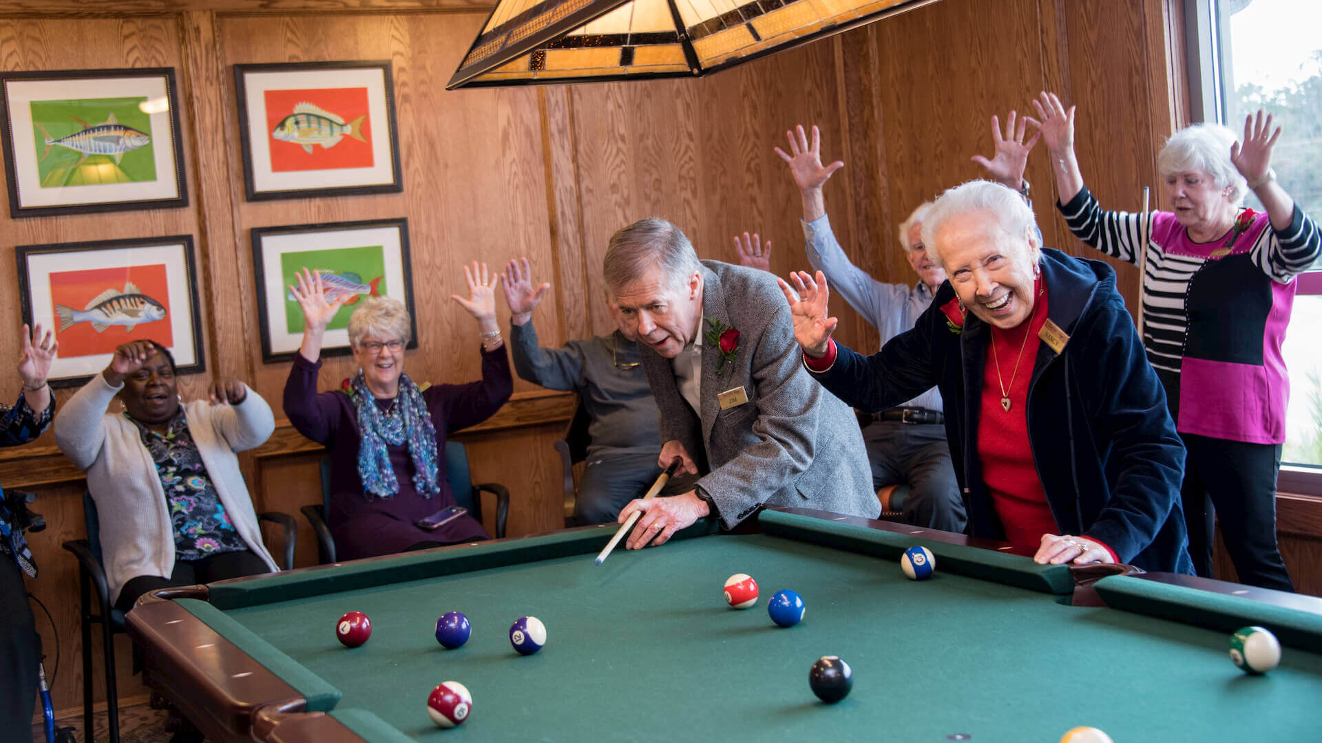 Senior friends celebrating a good shot in billiards.