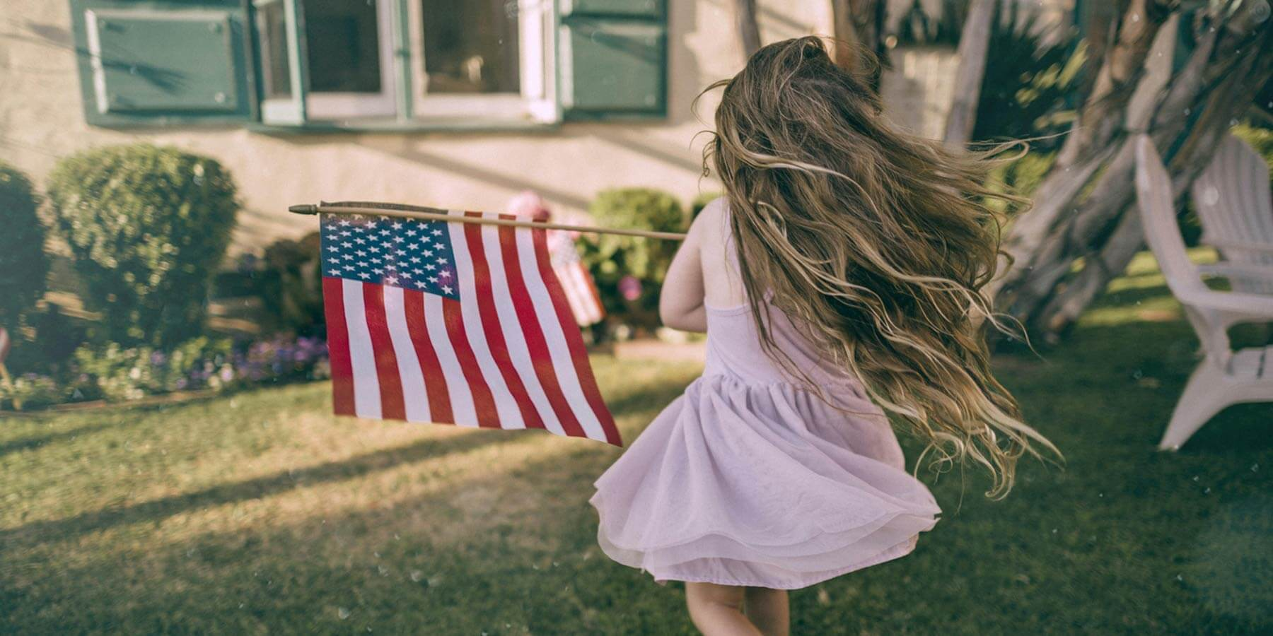 Little girl running around with an American Flag at a house.