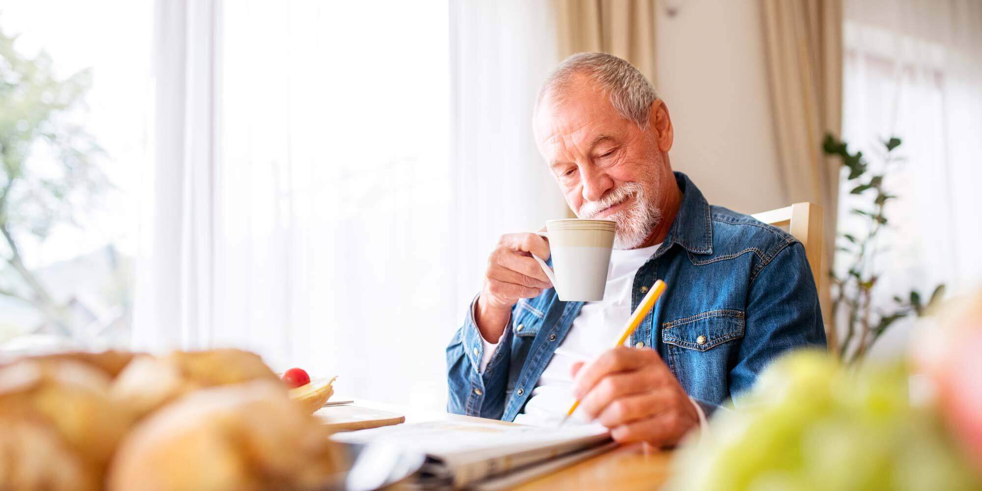 Resident enjoying a cup of coffee and a crossword puzzle.