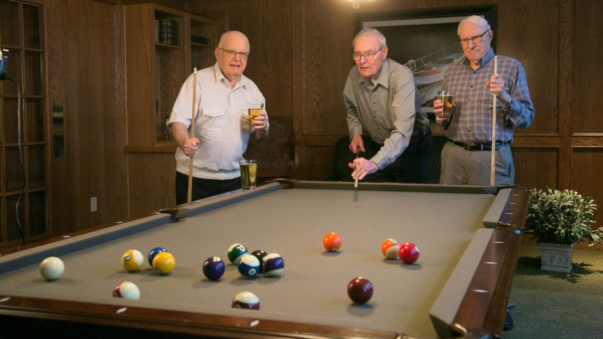 Senior friends playing billiards together, drinking beer.