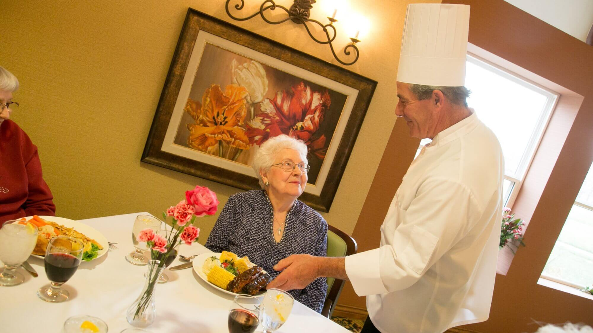 Chef presenting a delicious dish to a happy senior.