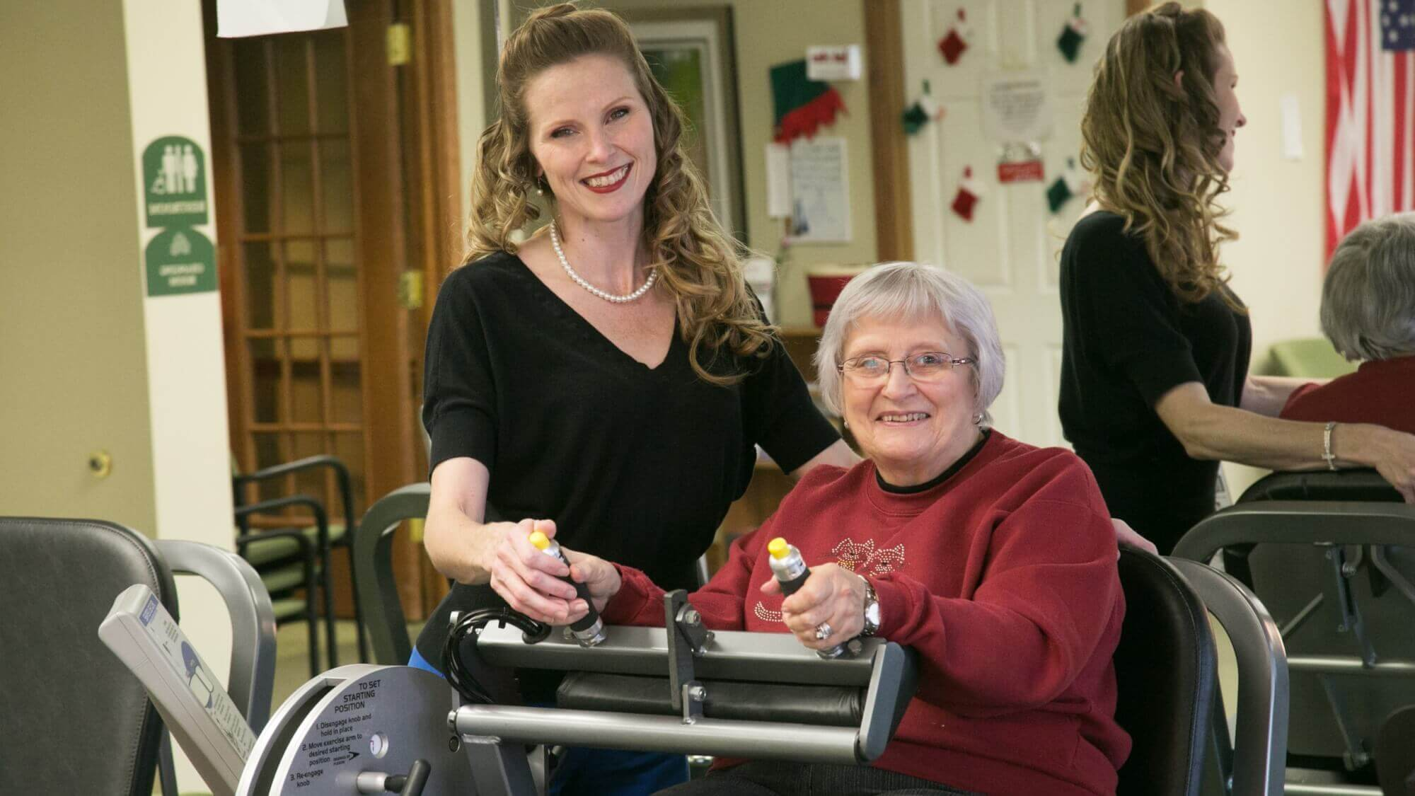 Happy senior in the fitness center with an employee.