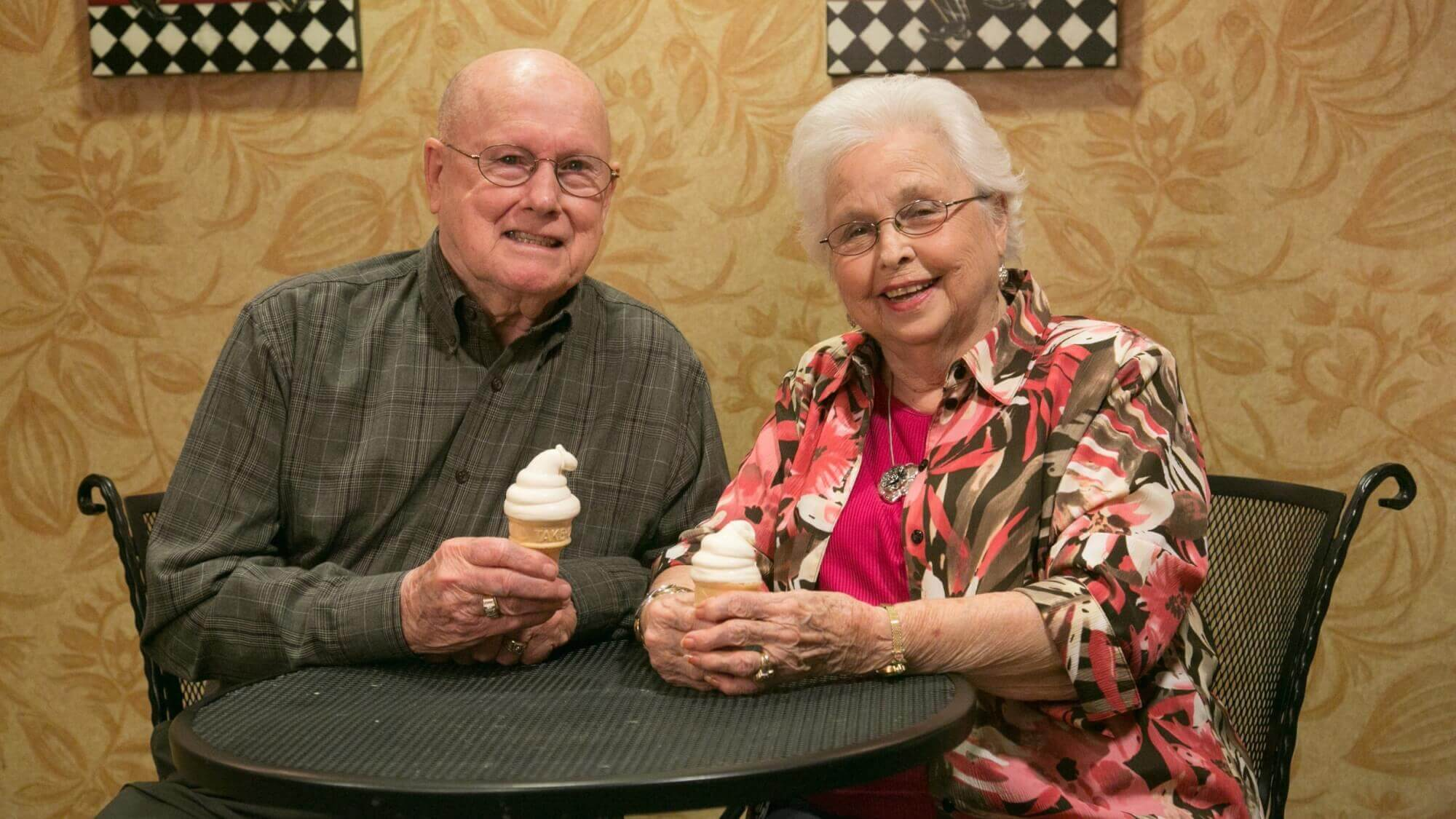 Happy senior couple sitting on a round table eating ice cream together.