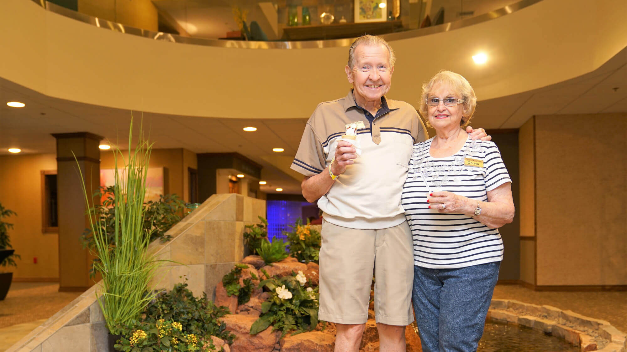 Happy senior couple standing in the main hall of Resort Lifestyle Communities eating ice cream.