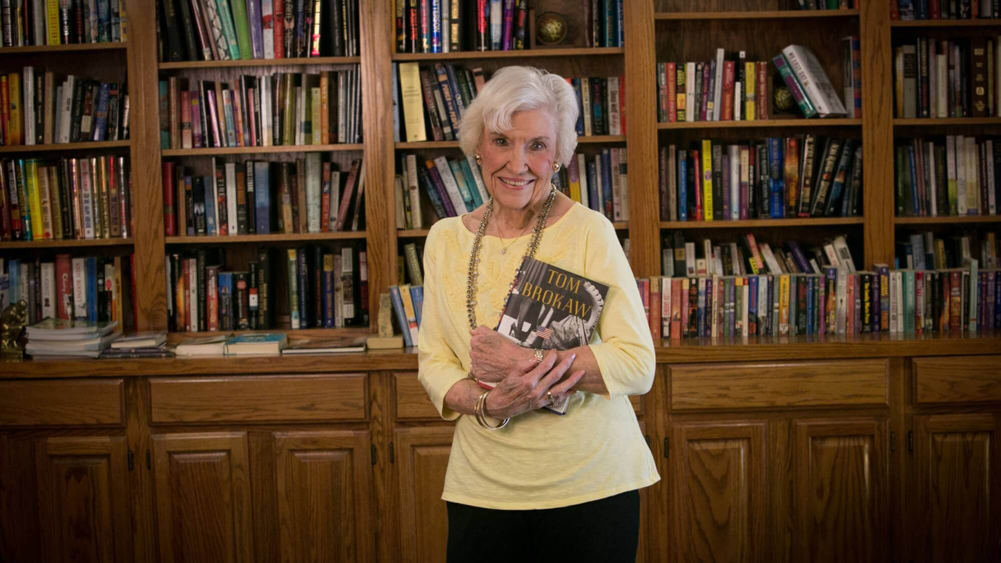 Happy senior holding a book in the library of Resort Lifestyle Communities
