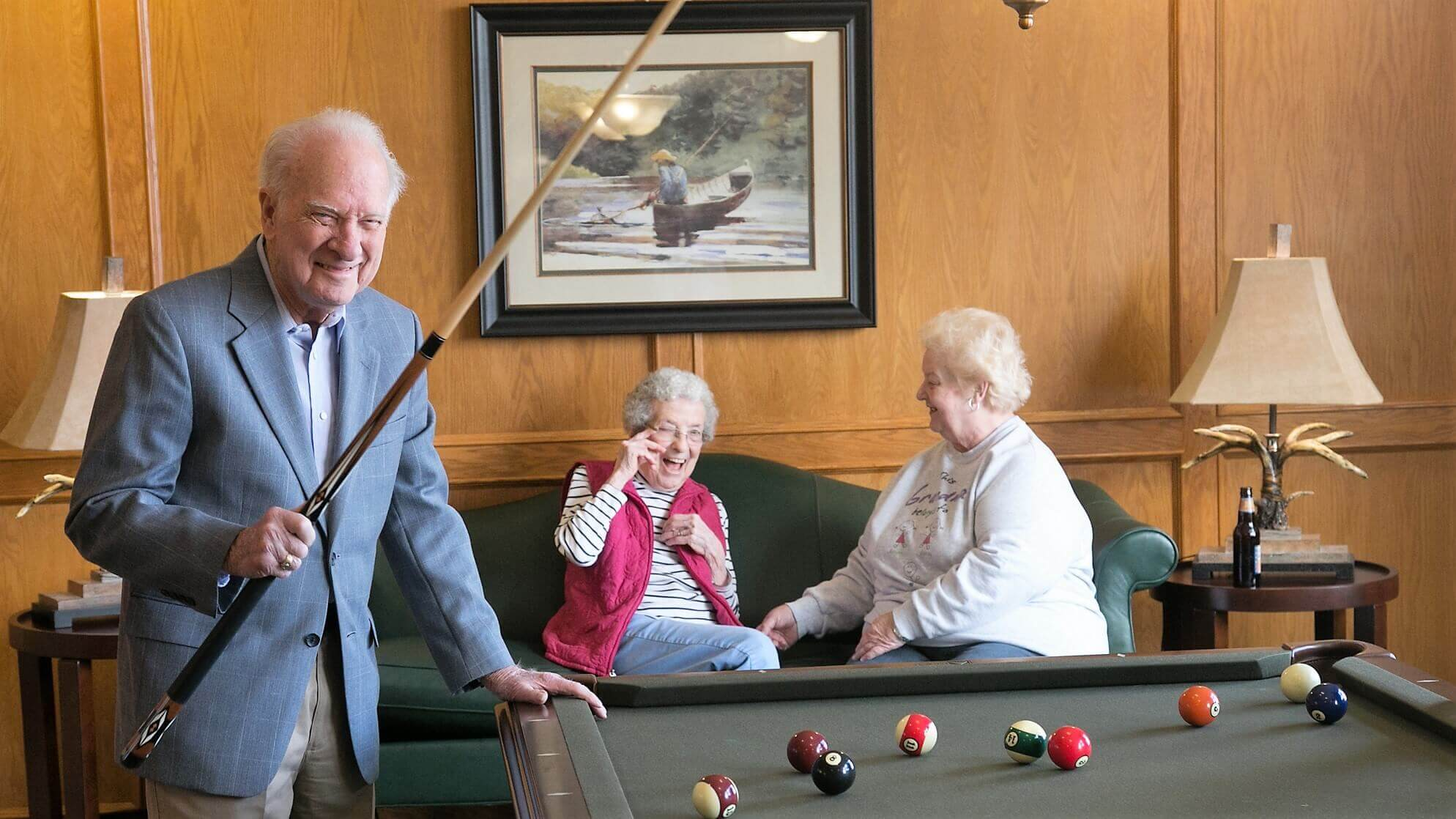 Happy senior friends laughing and playing billiards together.