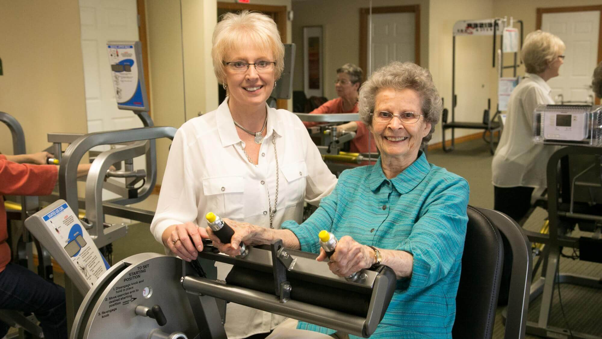 Happy senior learning how to use different machines in the fitness room at Resort Lifestyle Community.