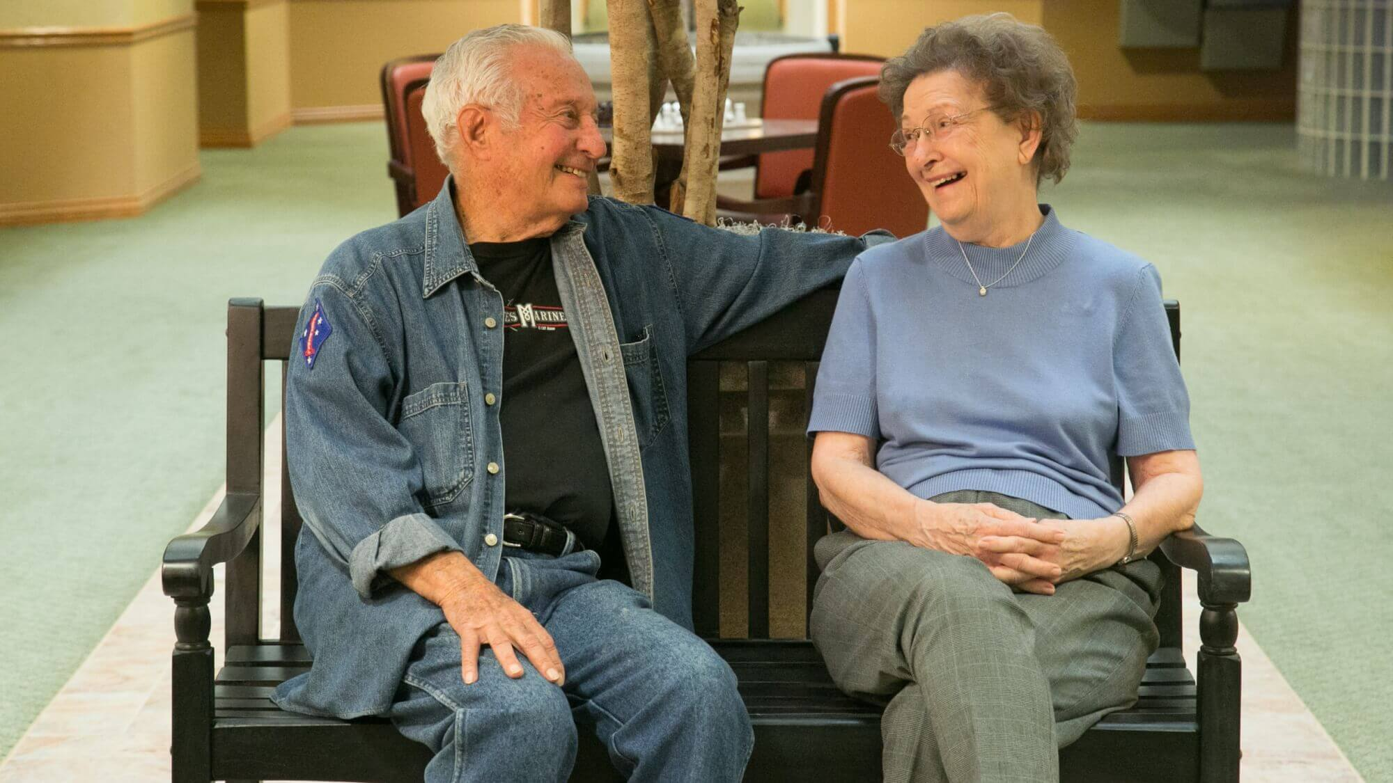 Happy senior couple sitting on a bench, smiling at one another.