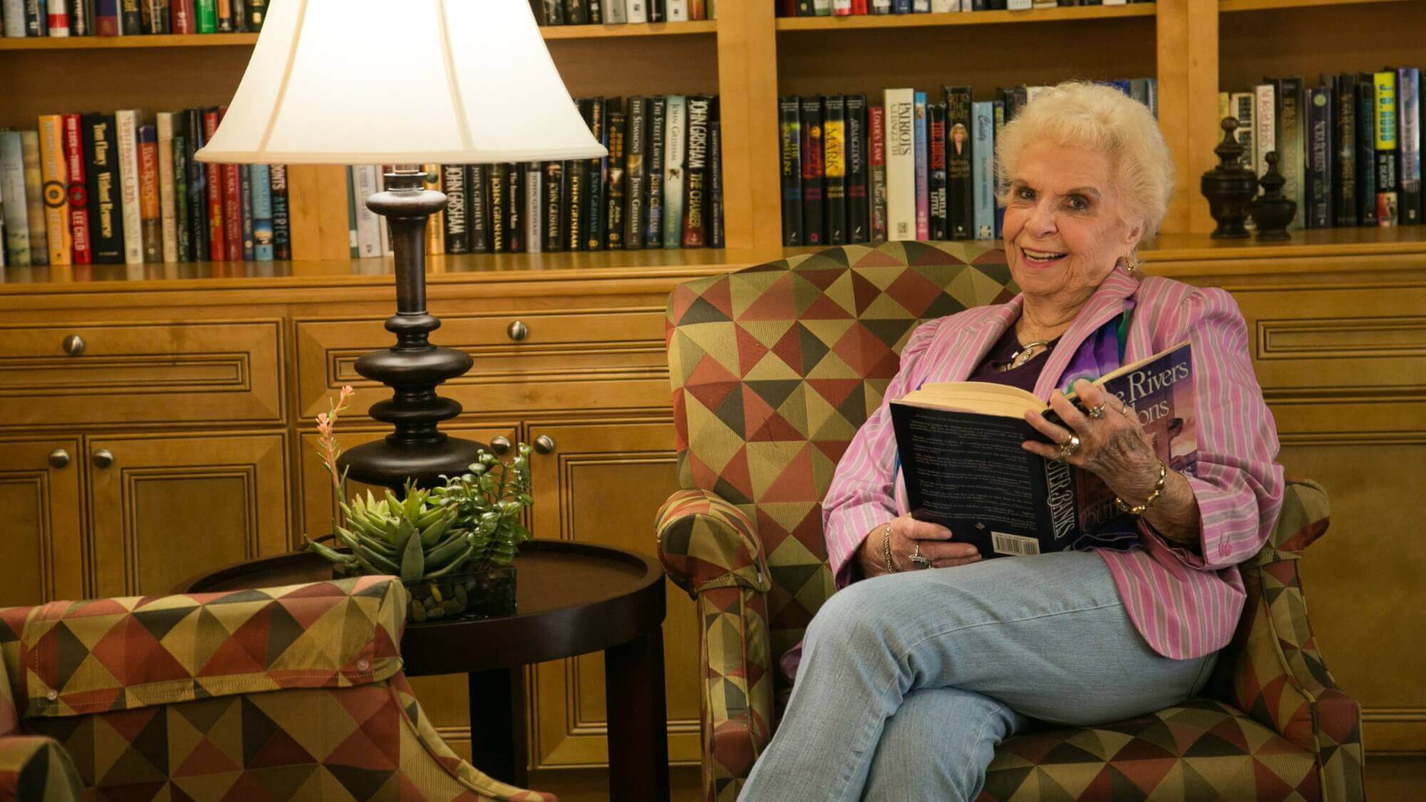 Senior in the library reading a book at Resort Lifestyle Community.