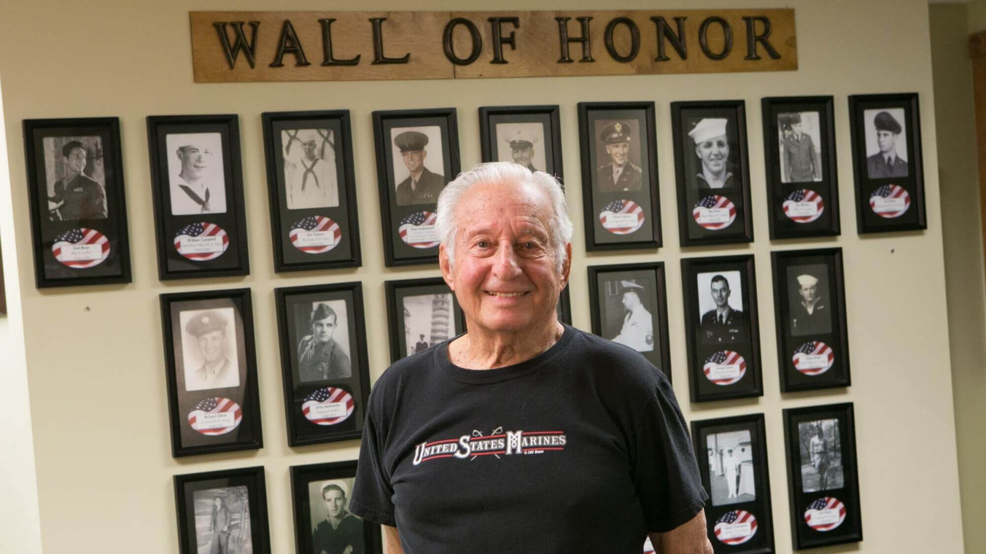 Senior veteran standing in front of the Wall of Honor at Resort Lifestyle Community.